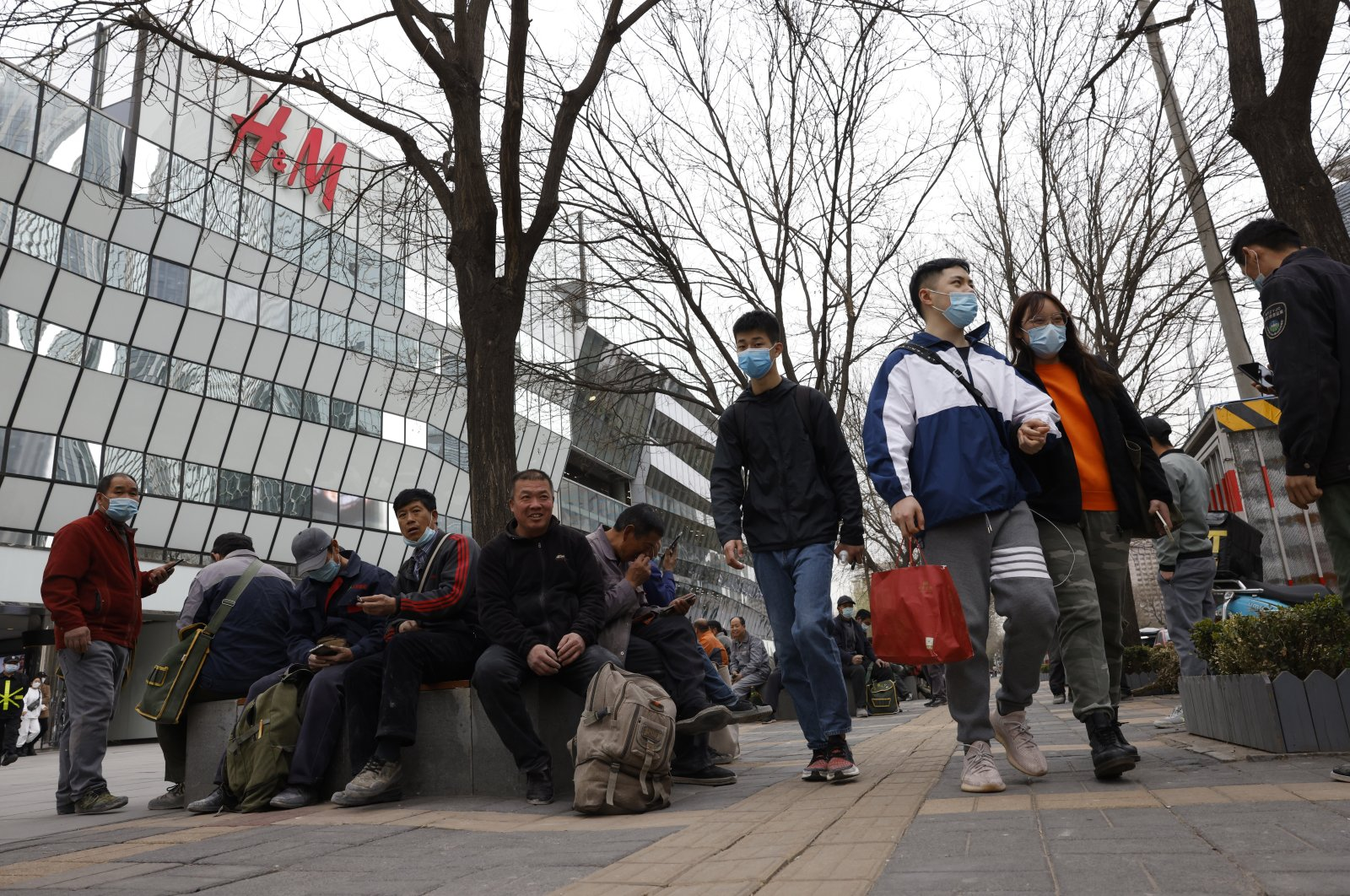 Visitors to a shopping mall wearing masks pass by an H&M store in Beijing, China, March 29, 2021. (AP Photo)