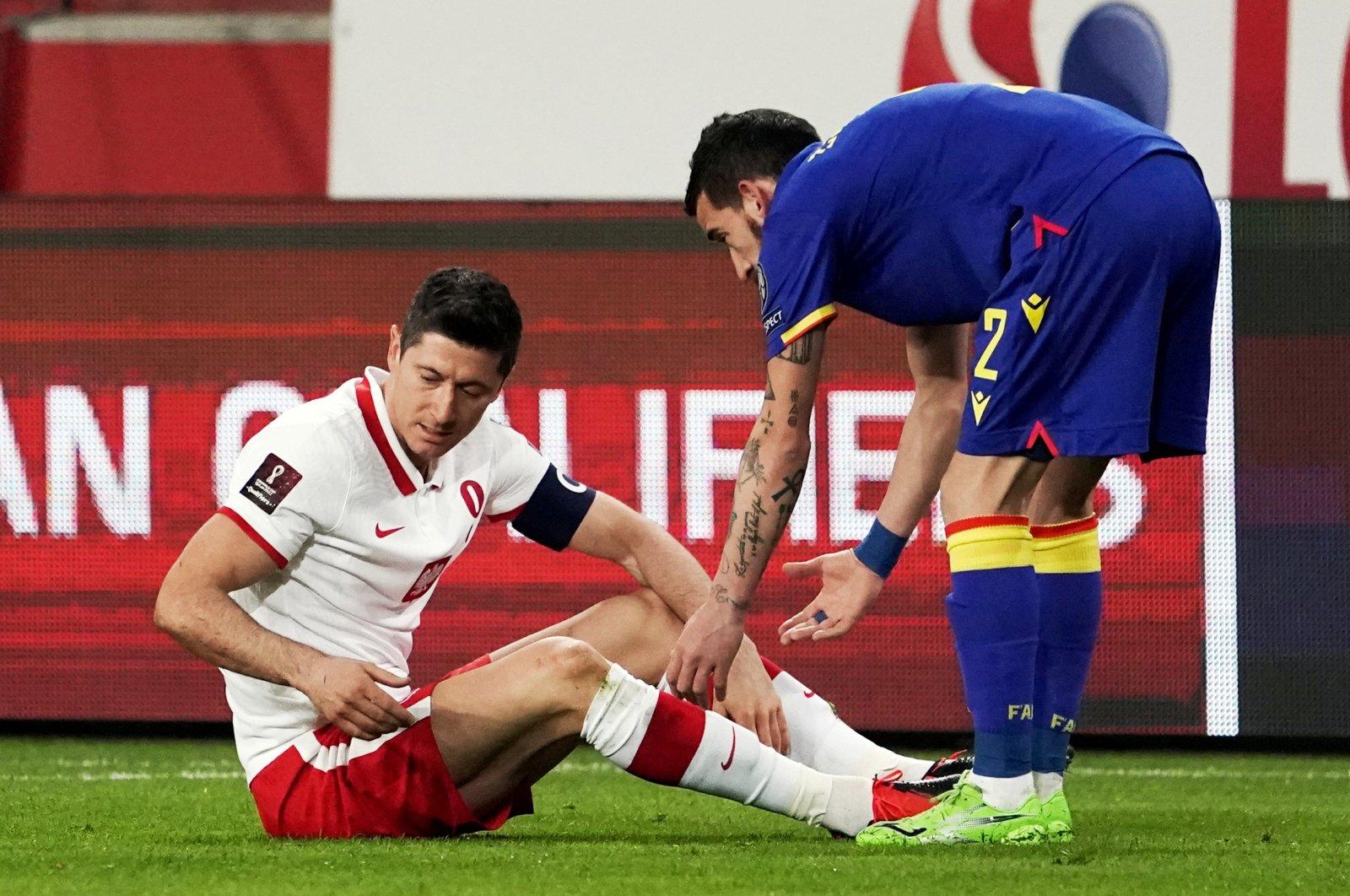 Poland's Robert Lewandowski (L) reacts after sustaining an injury as Andorra's Cristian Martinez looks on, Polish Army Stadium, Warsaw, Poland, March 28, 2021. (Reuters Photo)