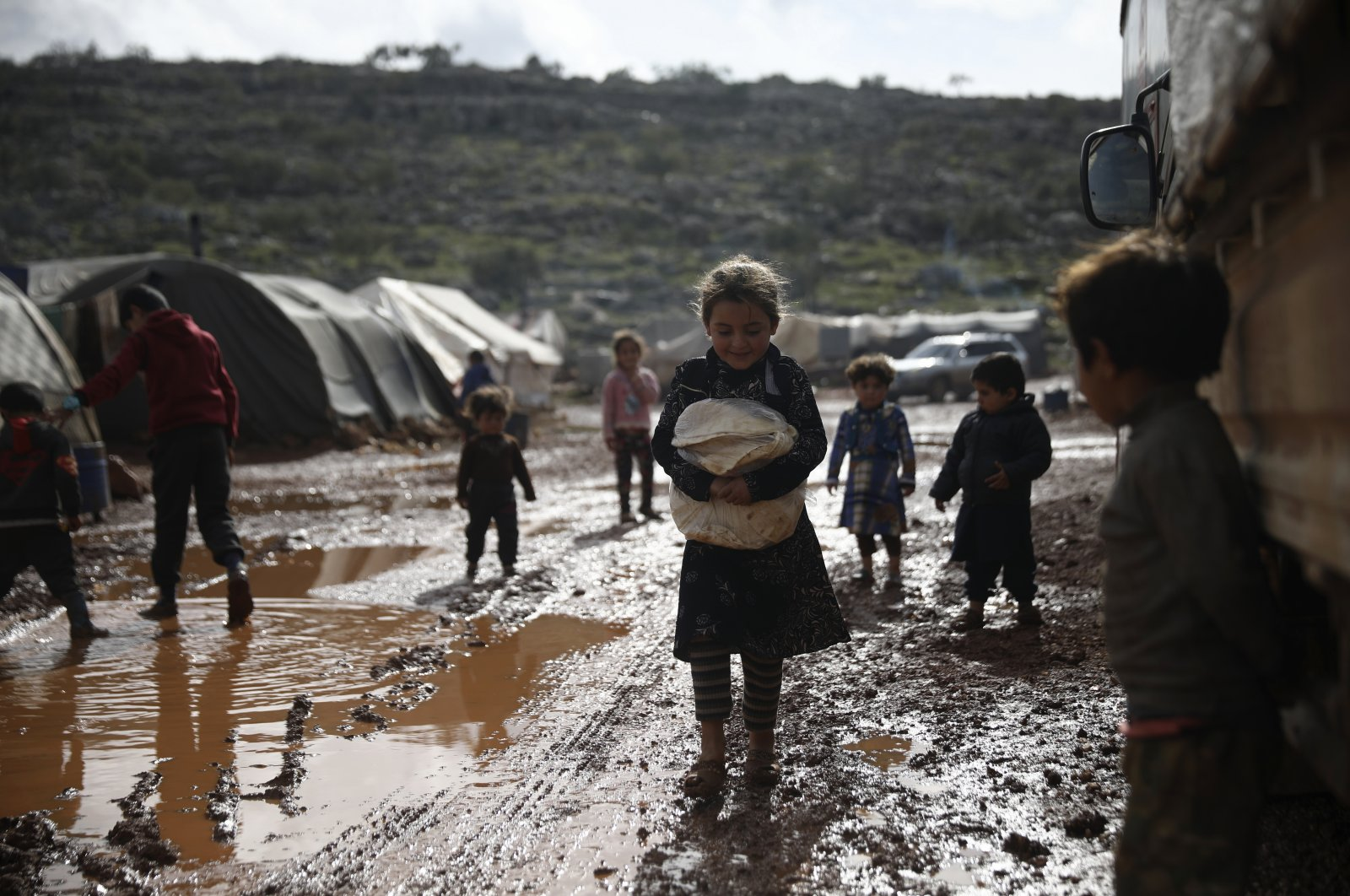 Syrian refugees walk through a camp for displaced people muddied by recent rains, in Idlib province, Syria, Jan. 28, 2021. (AP)