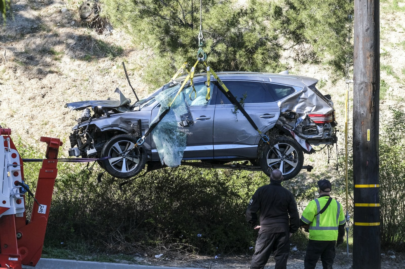 A crane is used to life a vehicle following an accident involving golfer Tiger Woods, in the Rancho Palos Verdes suburb of Los Angeles, California, U.S., Feb. 23, 2021. (AP Photo)