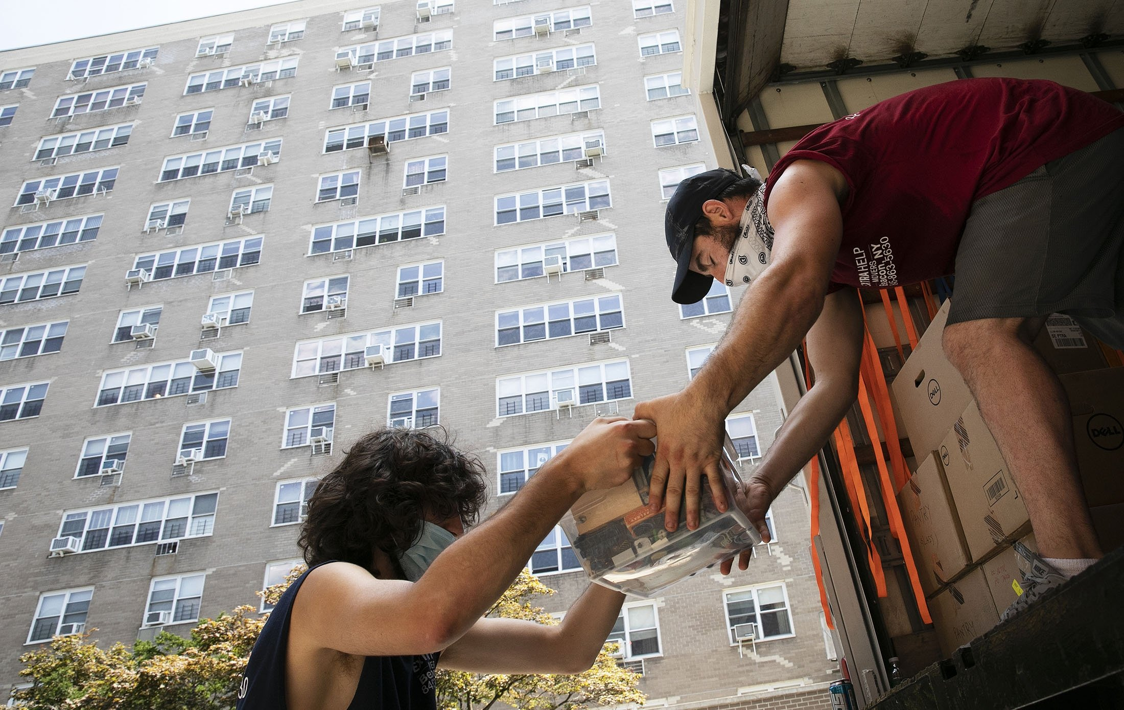 In this Tuesday, July 21, 2020 file photo, workers load boxes into a moving truck in The Bronx borough of New York for a family leaving their 14th-floor apartment amid the coronavirus pandemic. (AP Photo)