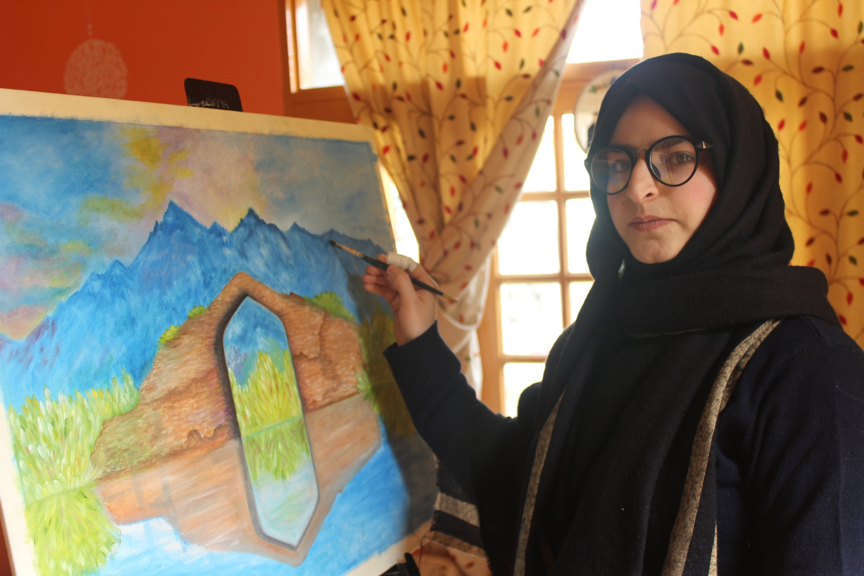 Afifa Makhdoomi paints a historical bridge of Kashmir at her home in Kashmir,  April 1, 2021. (AA Photo)