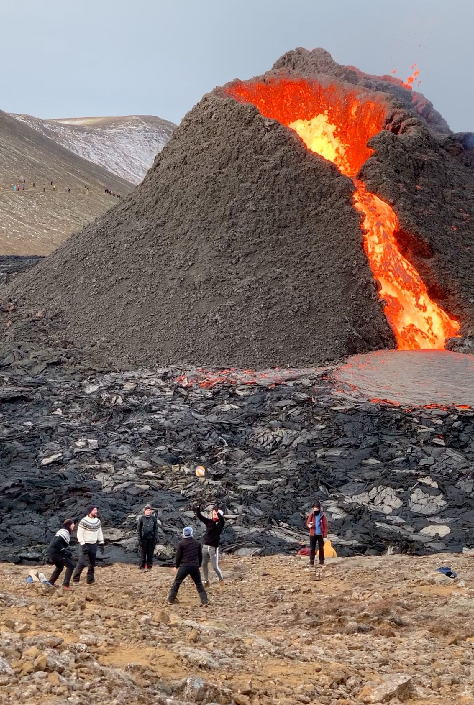 In this still image from a video posted on social media, people play volleyball near the lava-spewing Fagradalsfjall volcano in Reykjanes Peninsula, Iceland, March 27, 2021. (Rut Einarsdottir via Reuters)