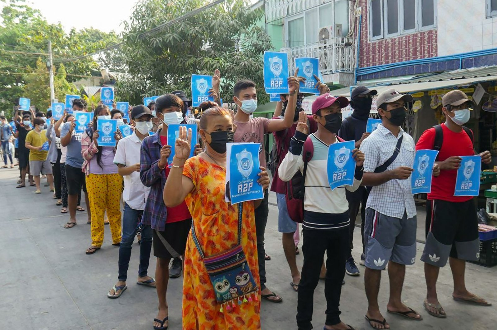 """Protesters hold signs relating to """"R2P,"""" or the """"Responsibility to Protect"""" principle that the international community should take action against a state that has failed to protect its population, in Yangon's Thaketa township, Myanmar, April 1, 2021. (AFP Photo)"""