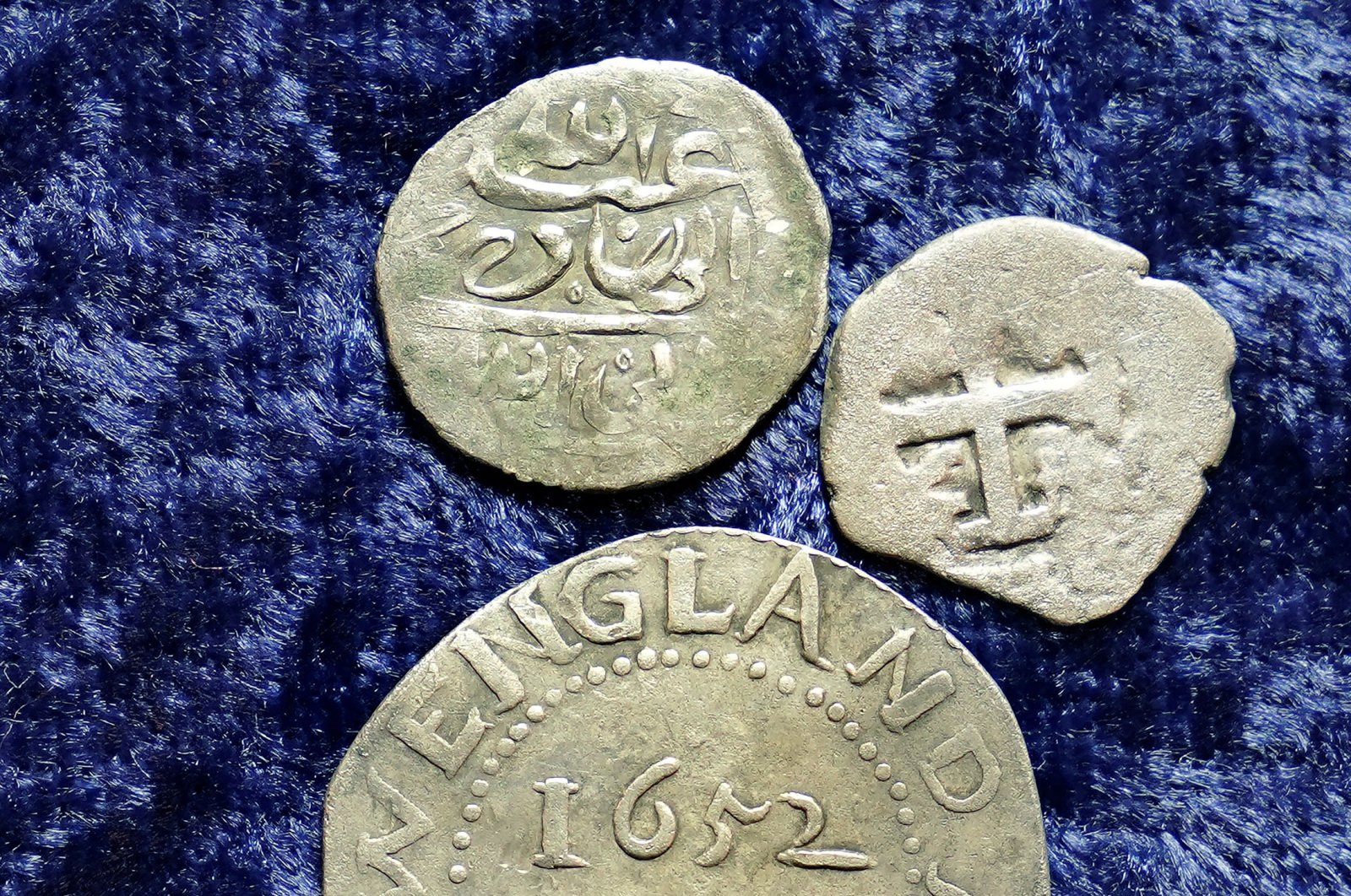 A 17th-century Arabian silver coin, top, that research shows was struck in 1693 in Yemen, rests near an Oak Tree Shilling minted in 1652 by the Massachusetts Bay Colony, below, and a Spanish half-real coin from 1727, right, on a table, in Warwick, Rhode Island, U.S., March 11, 2021. (AP Photo)