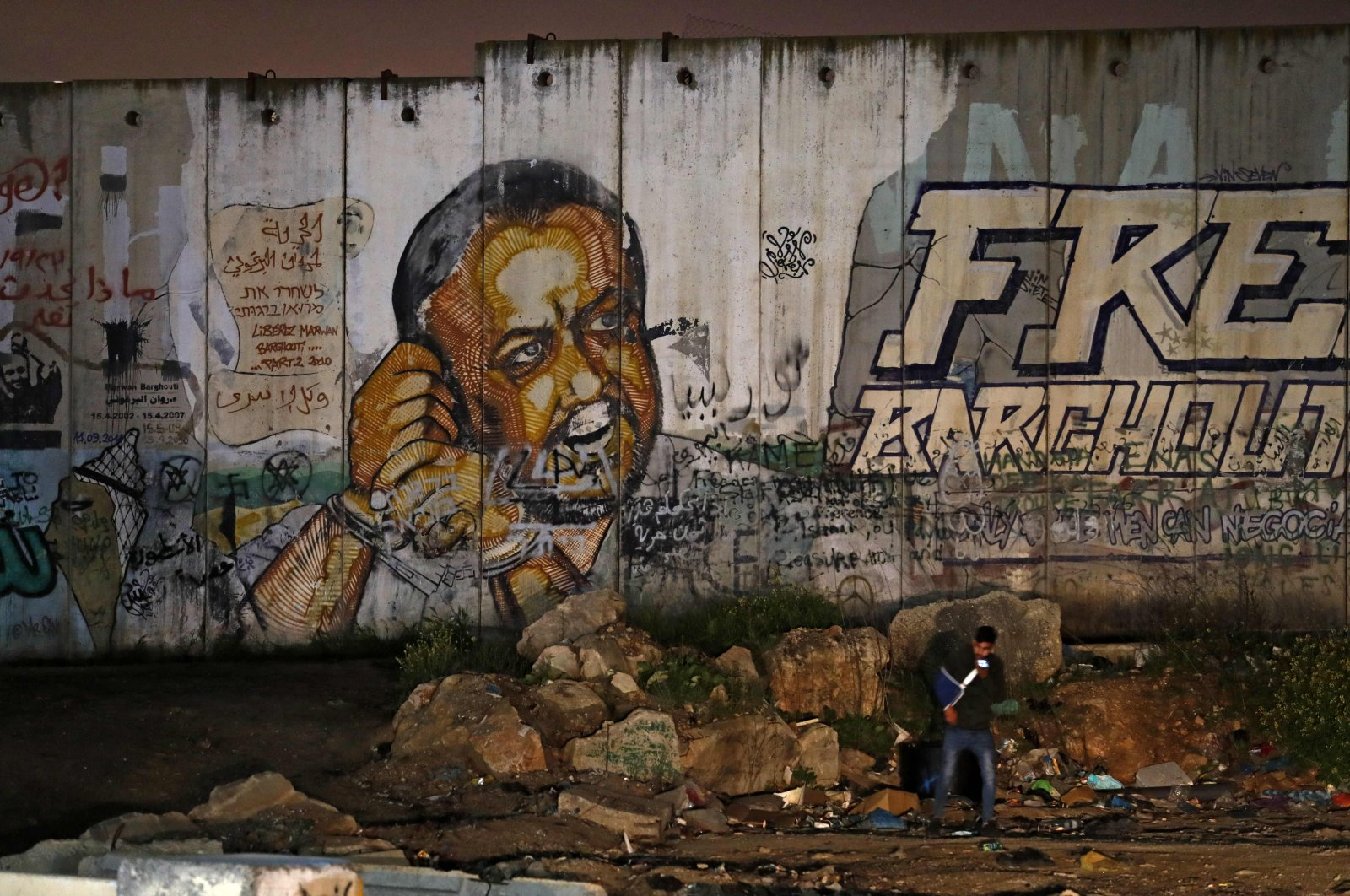 A mural of Fatah leader Marwan Barghouti on a section of Israel's controversial separation wall, near the Israeli Qalandiya checkpoint, between Jerusalem and Ramallah, March 31, 2021. (AFP Photo)