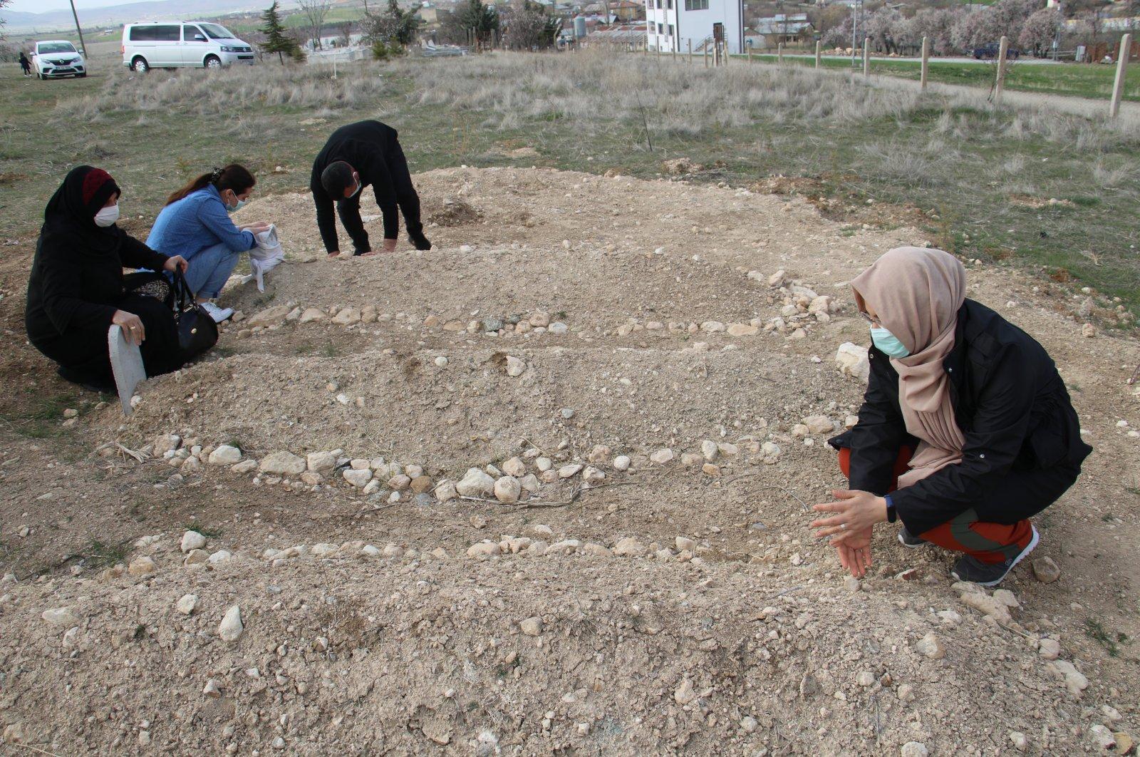 Relatives visit the graves of their family members, in Elazığ, eastern Turkey, April 1, 2021. (IHA PHOTO)