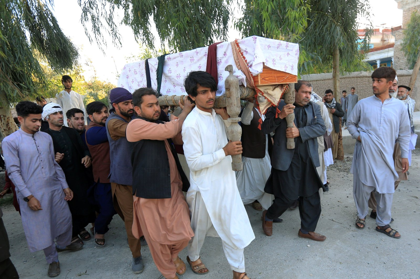A group of people carry the coffin of one of three female polio vaccination health workers who were shot and killed by unknown gunmen, during a burial ceremony in Jalalabad, Afghanistan, March 30, 2021. (Reuters Photo)