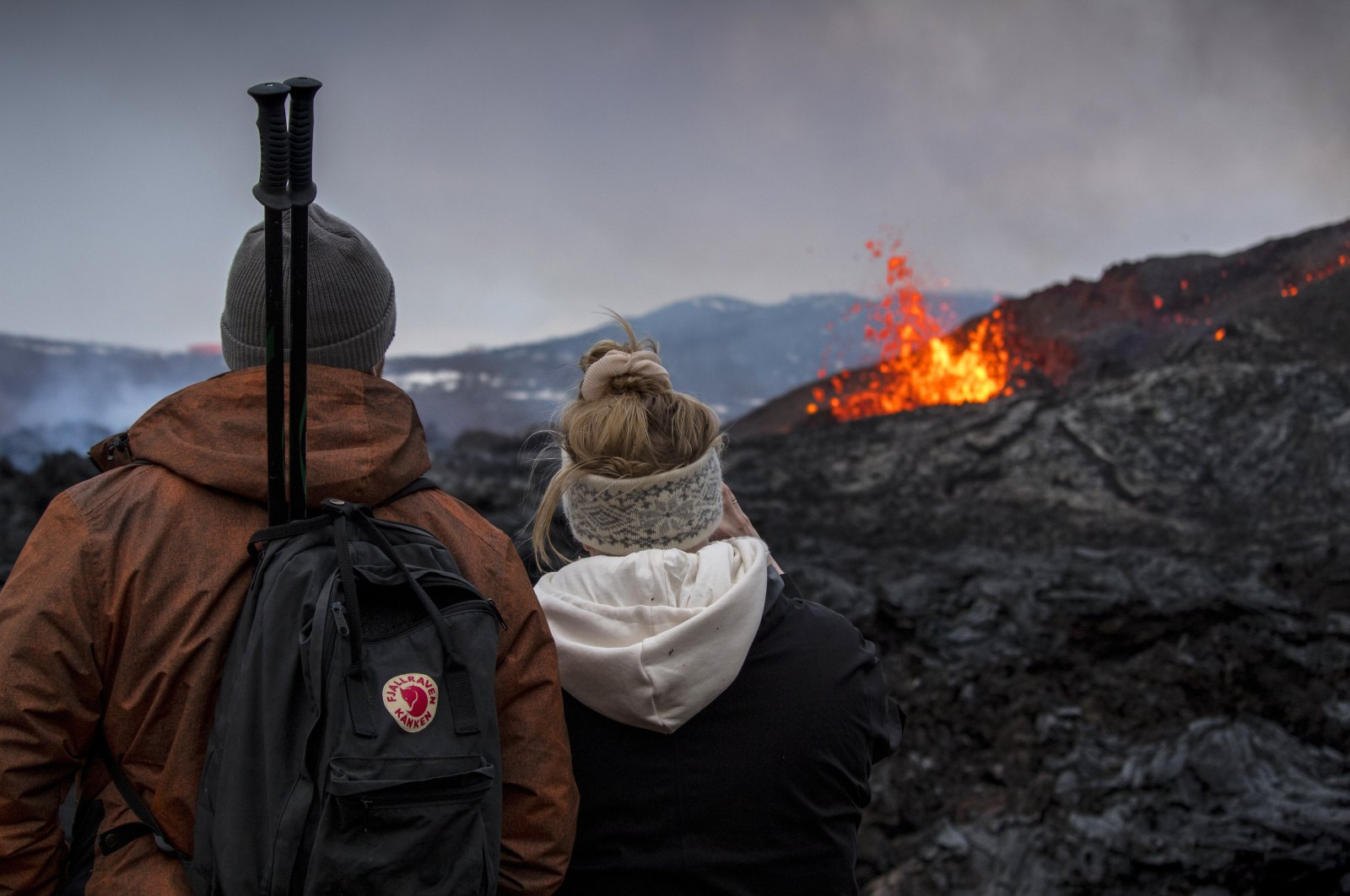People watch the Lava flows from an eruption of a volcano on the Reykjanes Peninsula in southwestern Iceland on Wednesday, March 31, 2021. (AP Photo)