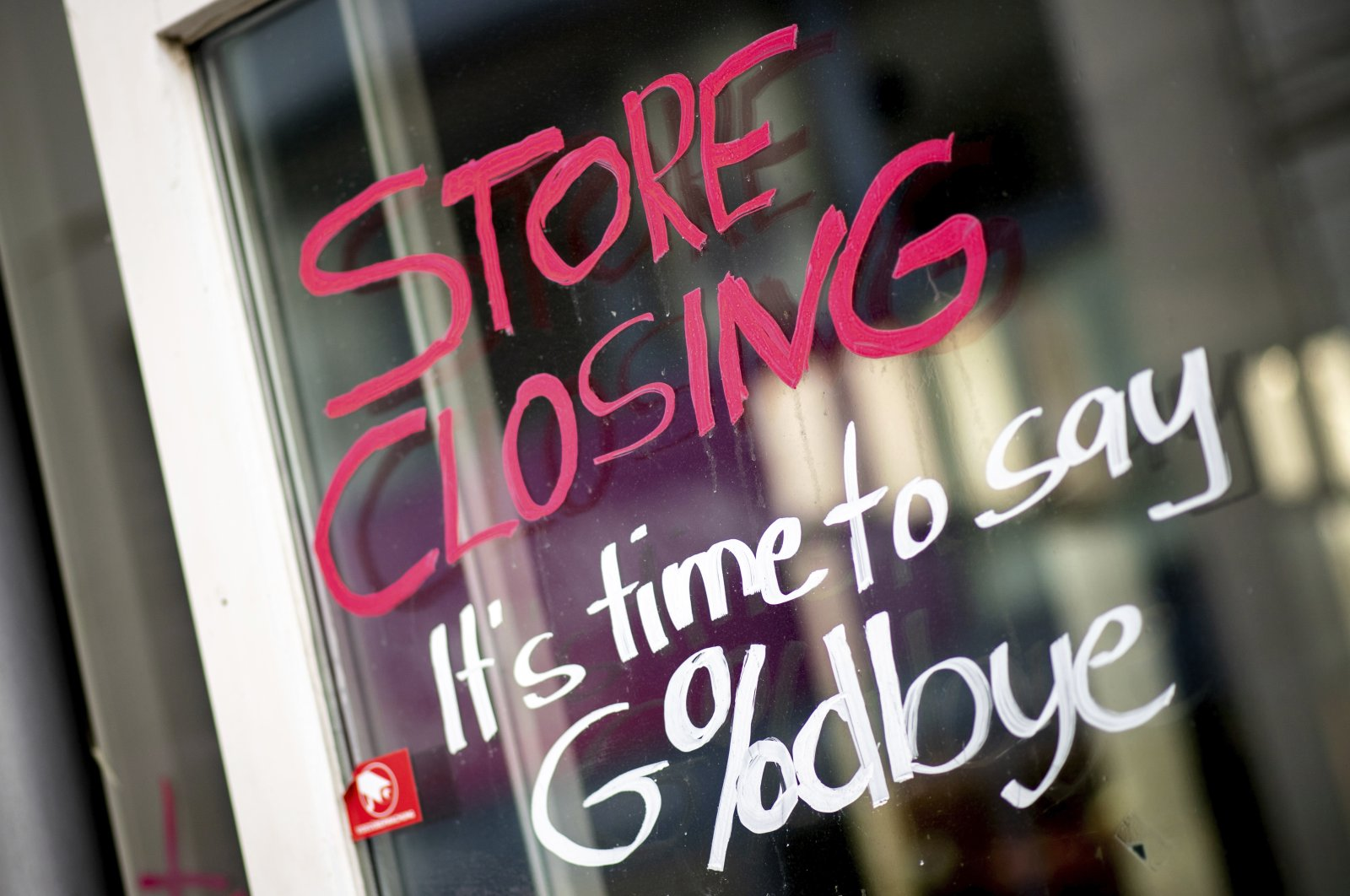 """The words """"Store Closing"""" and the addition """"It's time to say Goodbye"""" with a percent sign are written on the window of a closed store in the city center in Oldenburg, Germany, April 1, 2021. (AP Photo)"""