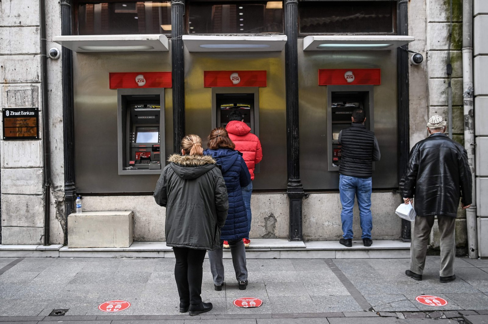 Customers wait in line to use ATMs of a Turkish bank near the Eminönü neighborhood in Istanbul, Turkey, March 22, 2021. (AFP Photo)