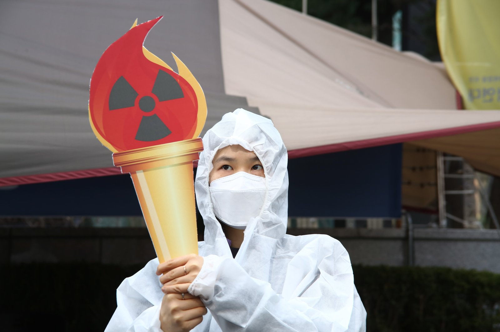 A member of an environmental group wearing a mock hazmat suit protests against Tokyo Olympics near the Japanese embassy in Seoul, South Korea, March 25, 2021. (EPA Photo)