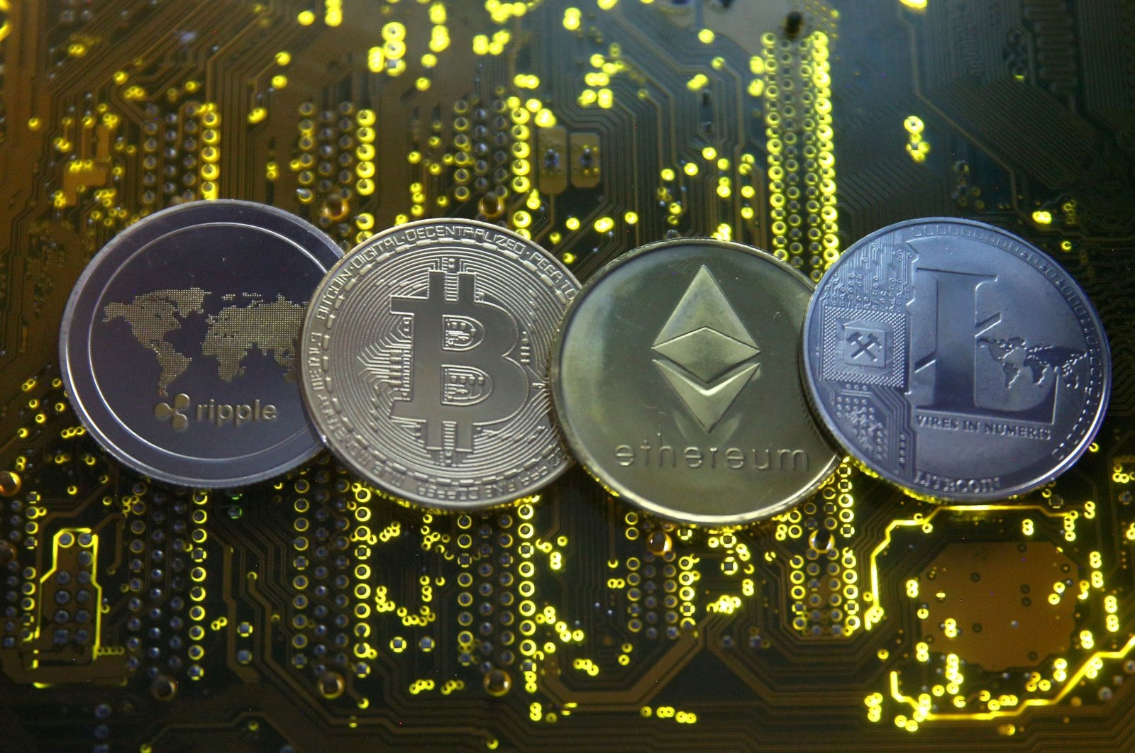 Representations of the Ripple, bitcoin, ethereum and Litecoin virtual currencies are seen on a PC motherboard in this illustration, Feb. 14, 2018. (Reuters Photo)