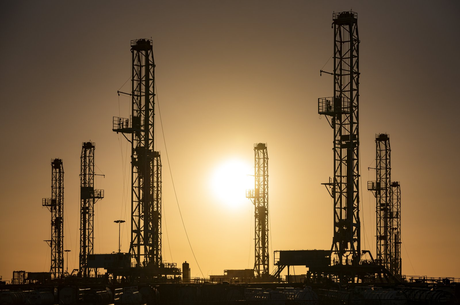 The morning sun rises behind oil rigs sitting in storage at a yard outside of Odessa, Texas, U.S., Feb. 6, 2021. (Odessa American via AP)