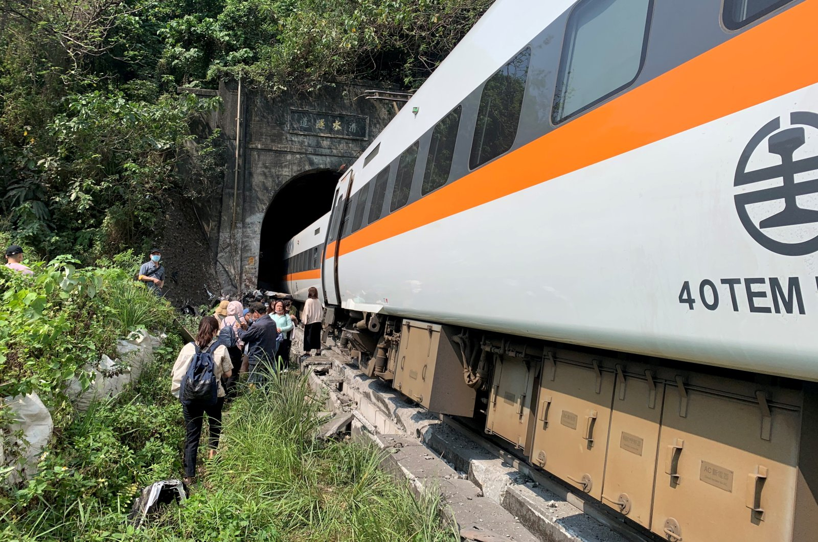 People walk next to a train which derailed in a tunnel north of Hualien, Taiwan, April 2, 2021, (Taiwan's National Fire Agency via Reuters)