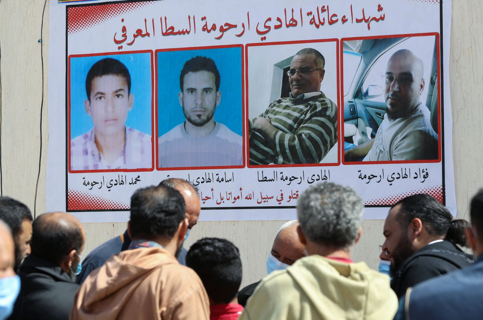 Libyans gather by a wall poster depicting victims from one family during a funeral procession for 12 bodies that were identified from mass graves found in Tarhuna, Libya, March 26, 2021. (AFP Photo)