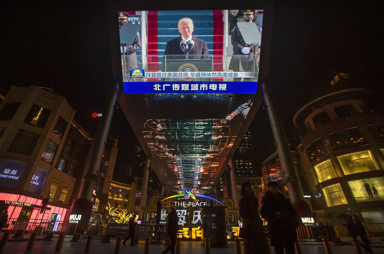 A large video screen shows a government news report about the inauguration of U.S. President Joe Biden at The Place shopping mall in Beijing, China, Jan. 21, 2021. (AP Photo)