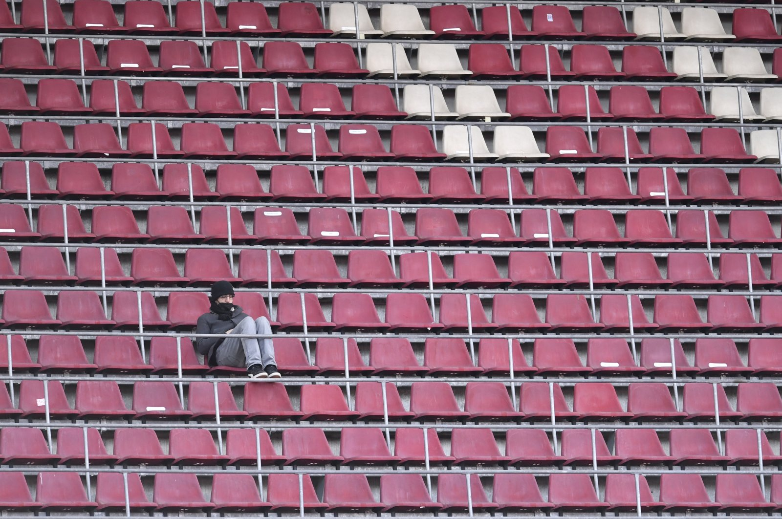 A person sits on the empty stands during the German Bundesliga match between Cologne and Dortmund at the RheinEnergieStadion stadium, Cologne, Germany, March 20, 2021. (AP Photo)