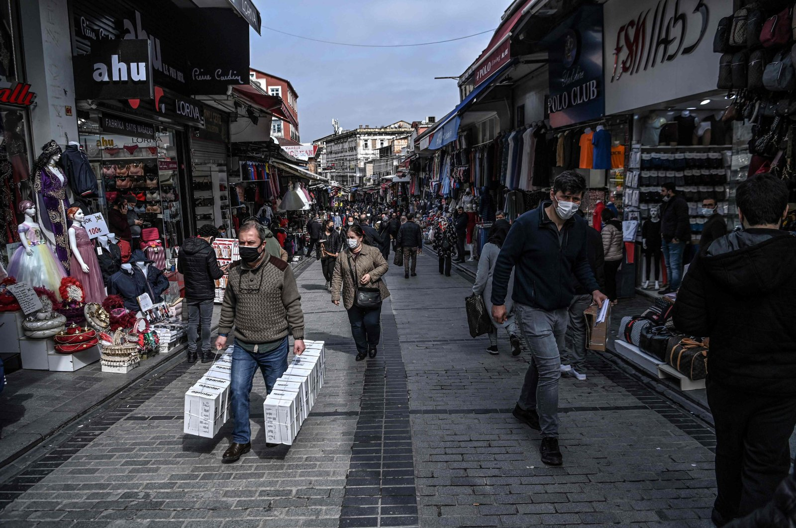 Pedestrians and customers walk past shops in the Mahmutpaşa neighborhood in Istanbul, Turkey, March 22, 2021. (AFP Photo)