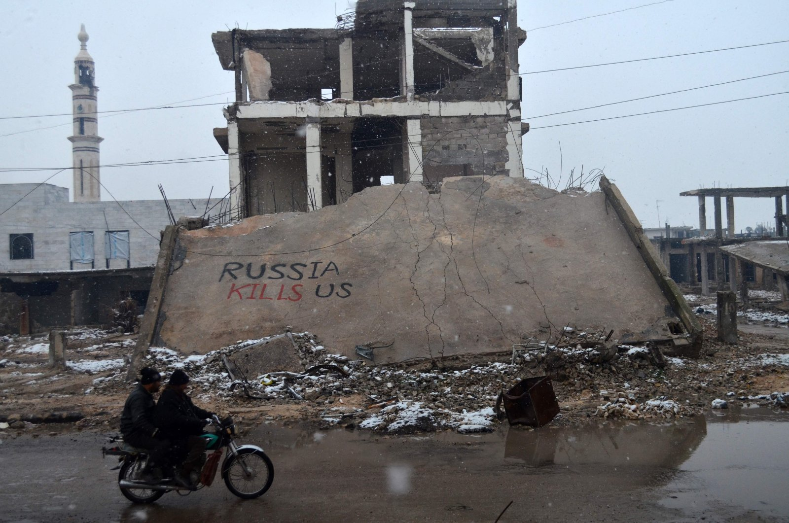 """Syrians ride a motorbike past a collapsed building with graffiti reading """"Russia kills us"""" in the central Syrian town of Talbisseh in Homs province, Syria, Jan. 1, 2016. (AFP Photo)"""