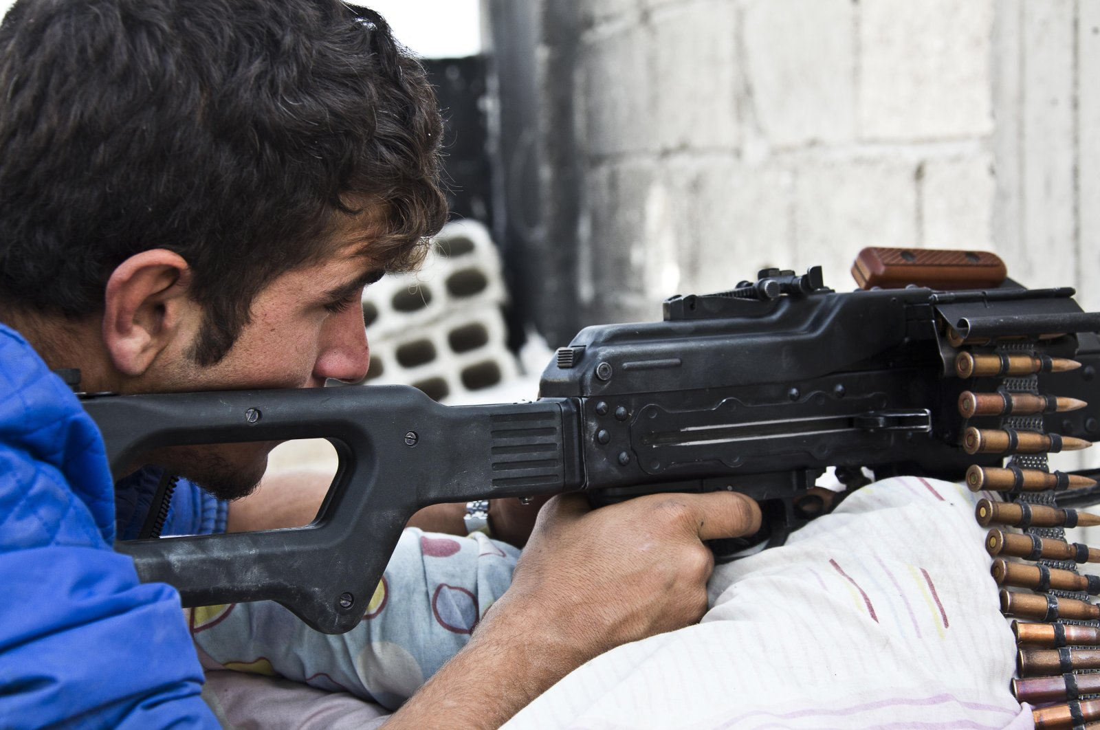 A young member of the YPG who recently volunteered for the terrorist group holds a position with his weapon in Kobani, Syria, Nov. 19, 2014. (AP Photo)