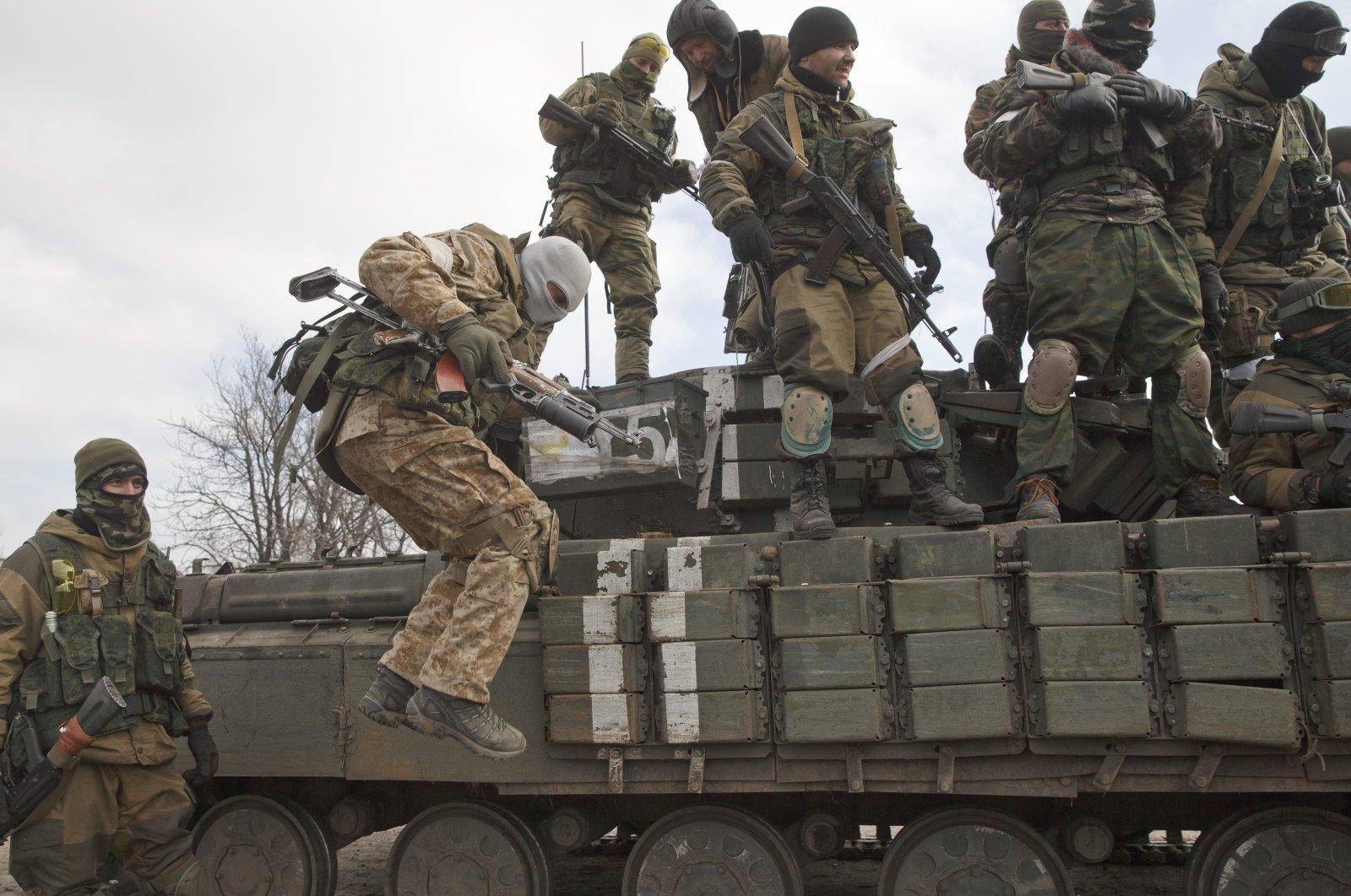 A Russia-backed rebel jumps off a tank in Debaltseve, Ukraine, Feb. 20, 2015. (AP Photo)