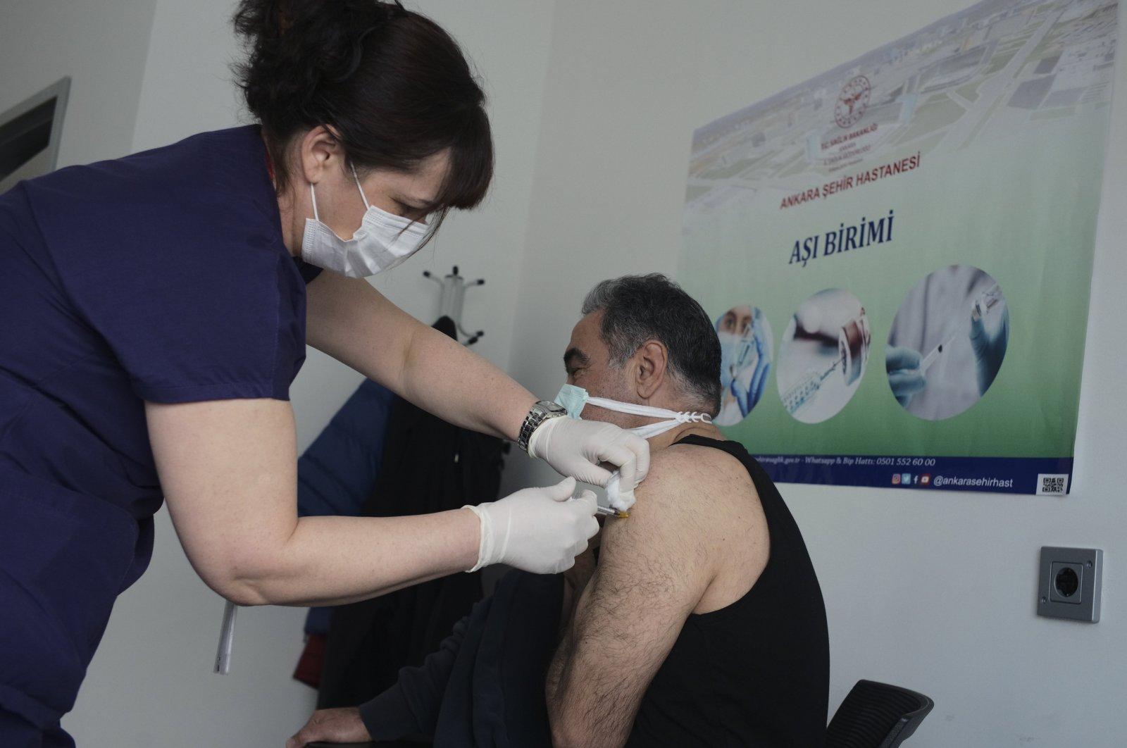 Nurse Fatma Gökçe administers the Pfizer/BioNtech COVID-19 vaccine to a person at a hospital, Ankara, Turkey, Saturday, April 3, 2021. (AP Photo)
