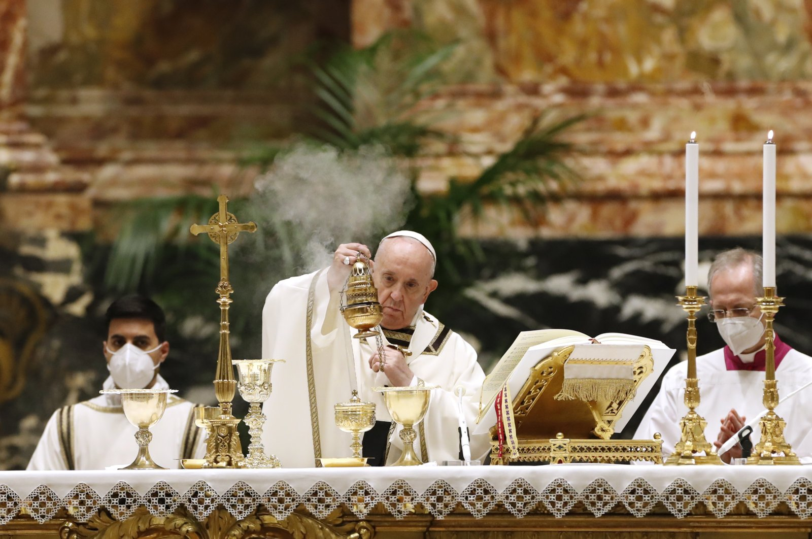 Pope Francis celebrates the Easter Vigil in a nearly empty St. Peter's Basilica as coronavirus pandemic restrictions stay in place for a second year running, the Vatican, Saturday, April 3, 2021. (AP Photo)