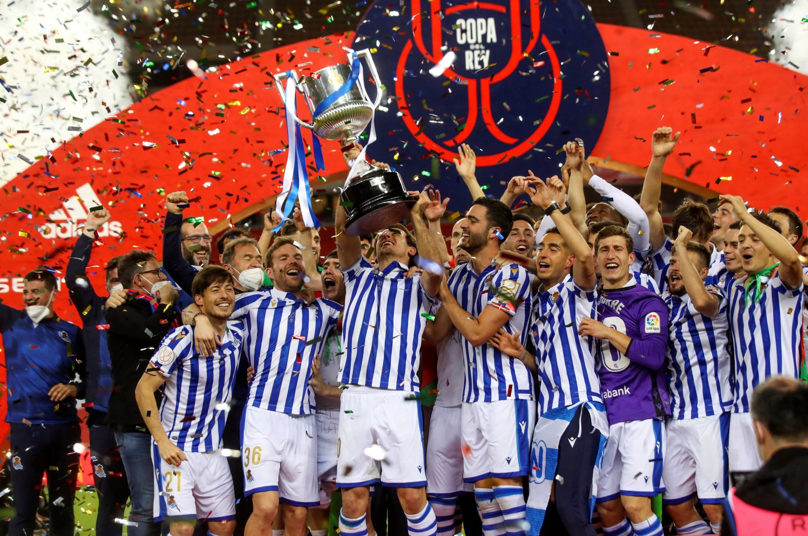 A handout photo made available by the Spanish Royal Soccer Federation (RFEF) shows Real Sociedad players after receiving the trophy from Spain's King Felipe VI (CL) after winning the 2020 Copa Del Rey final match against Athletic Bilbao at La Cartuja stadium in Seville, Andalusia, Spain, April 03, 2921. (RFEF via EPA)