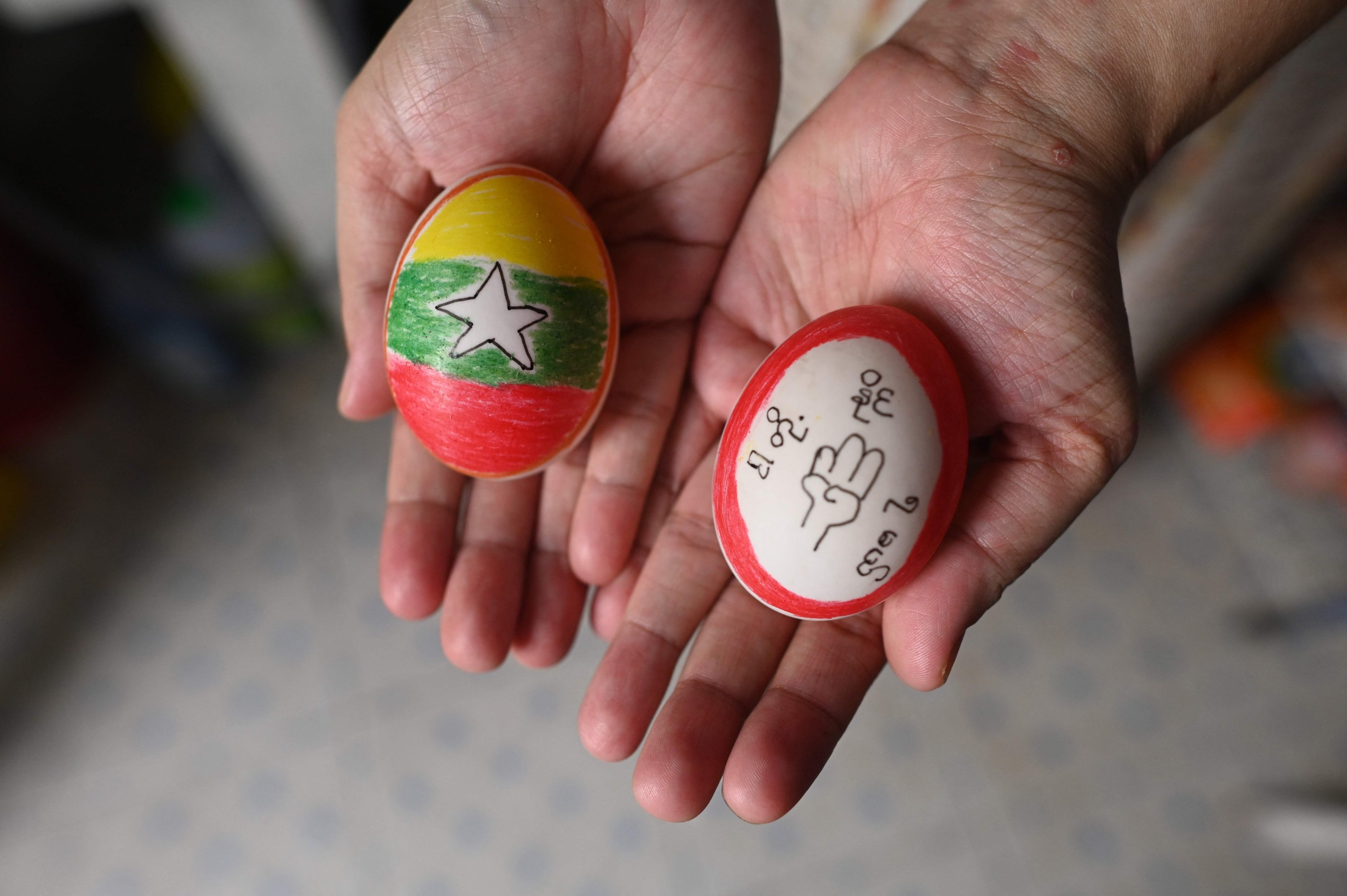 A person displays eggs, decorated with messages in support of protesters demonstrating against the military coup, in Yangon's Mingalar Taungnyunt township, Myanmar, April 4, 2021. (AFP Photo)