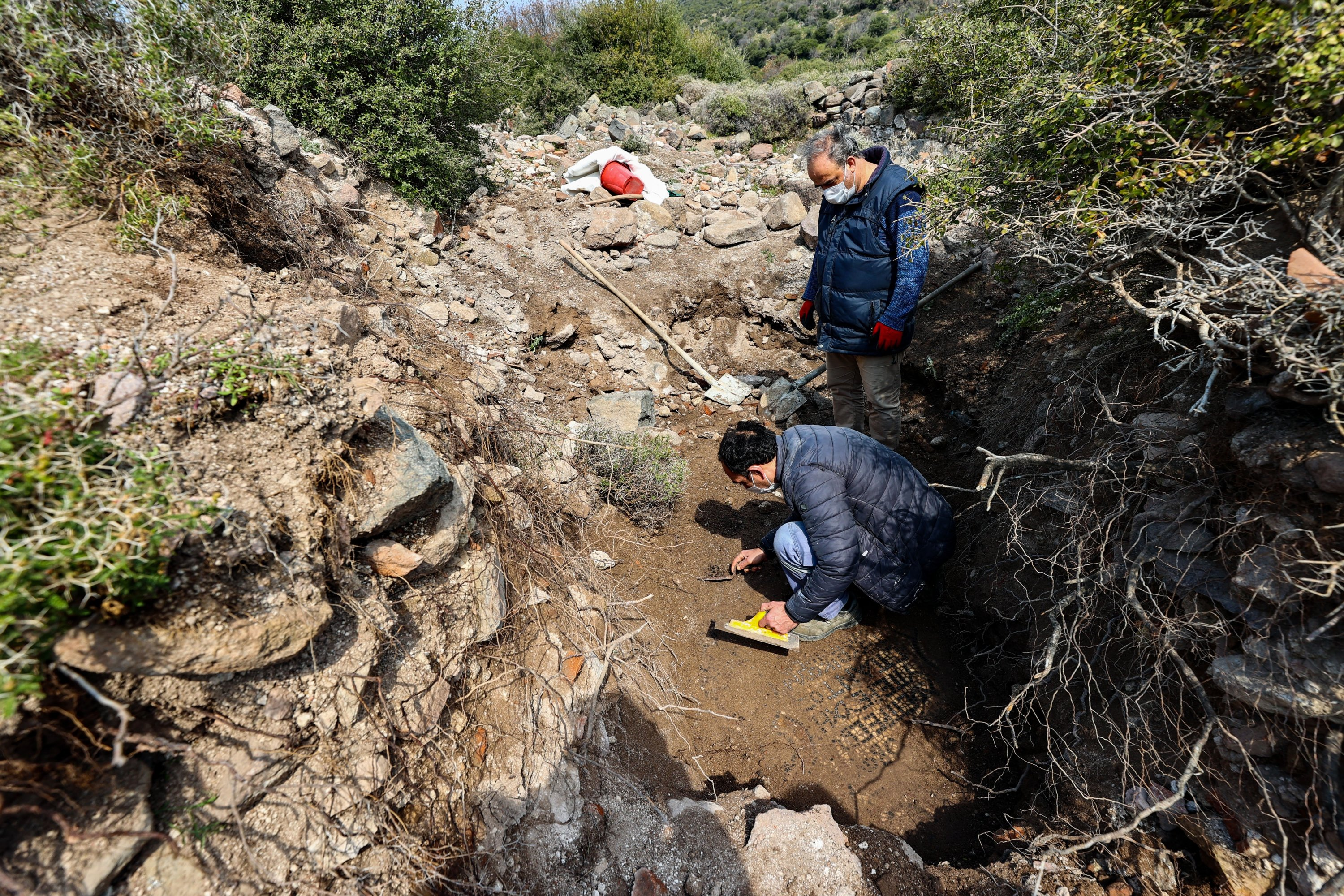 Two experts from the Izmir Archeology Museum investigate the area where the mosaic and monastery unearthed, Izmir, western Turkey, April 3, 2021. (AA Photo)