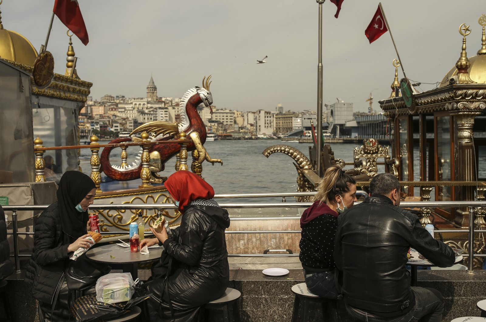 People enjoy a snack amid the COVID-19 restrictions, in the Eminönü district, Istanbul, Turkey, April 2, 2021. (AP Photo)