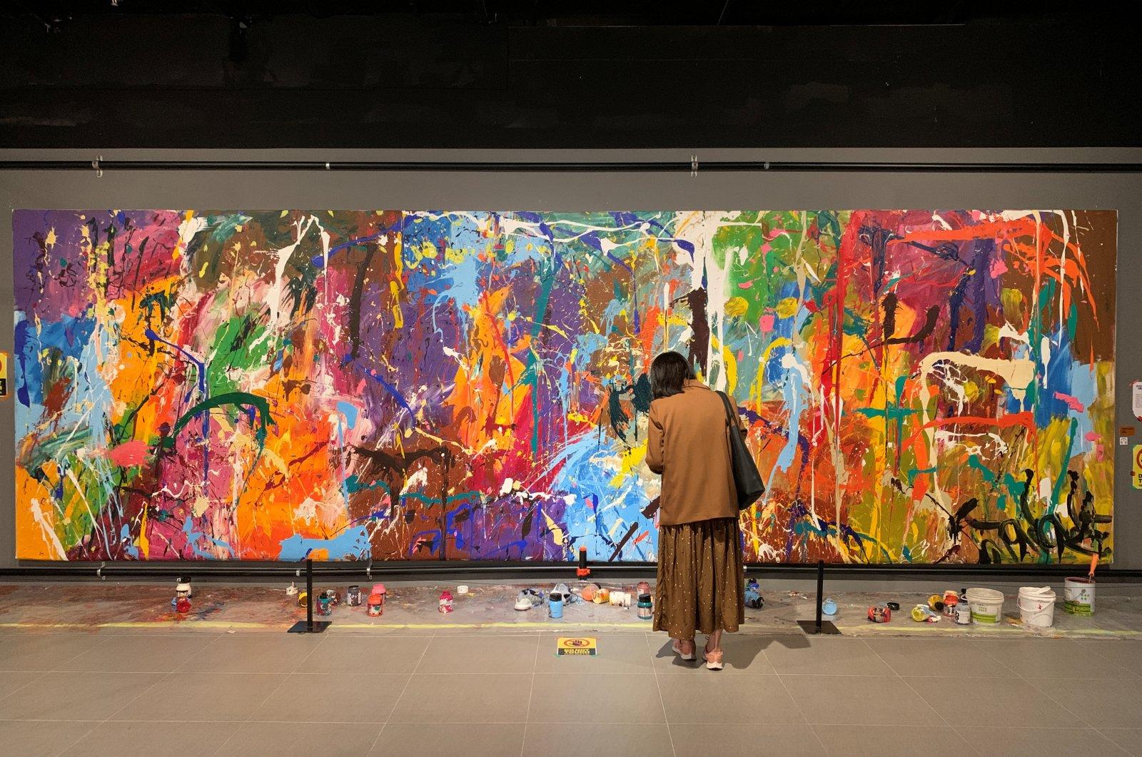 A visitor looks at the graffiti artwork of New York-based artist Jon One, Seoul, South Korea, April 2, 2021. (REUTERS Photo)