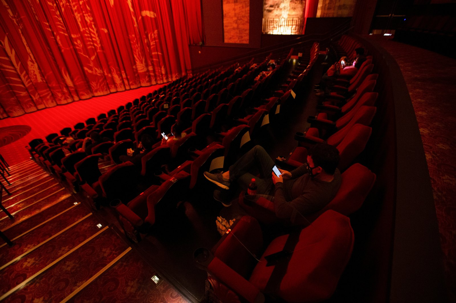 """Moviegoers sit socially distanced as they wait for the movie """"Godzilla vs. Kong"""" on the reopening day of the TCL Chinese theater during the outbreak of the coronavirus, Los Angeles, California, U.S., March 31, 2021.  (Reuters Photo)"""