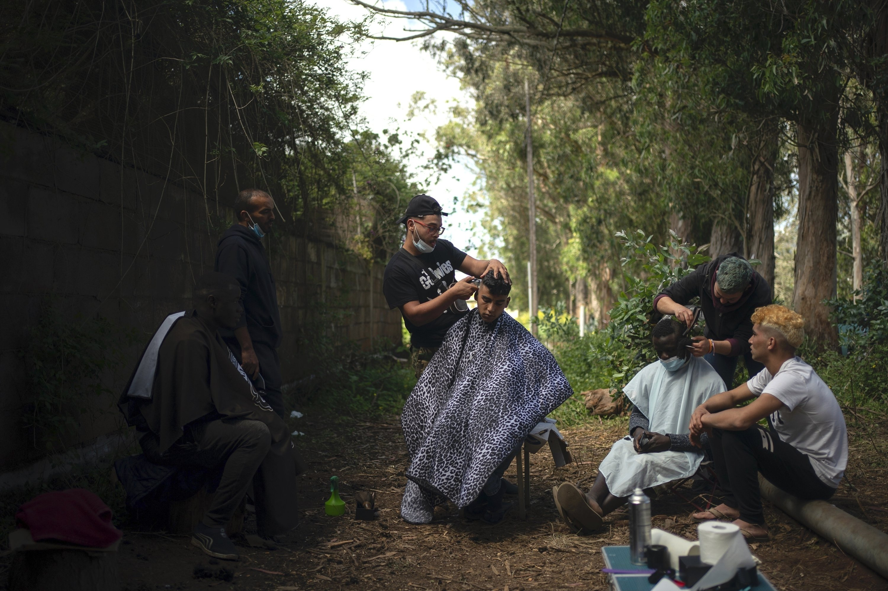 Yassime, 29, from Morocco cuts the hair of Ibrahim, 22, also from Morocco outside the Las Raices camp in San Cristobal de la Laguna, in the Canary Island of Tenerife, Spain, March 19, 2021. (AP Photo)