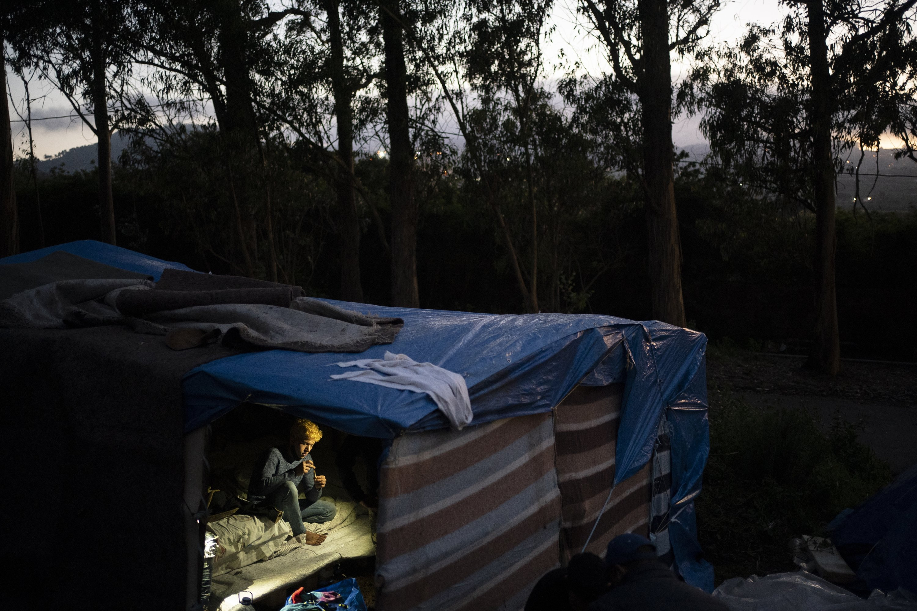 A migrant rests in a makeshift shelter in Las Raices camp in San Cristobal de la Laguna on the Canary Island of Tenerife, Spain, March 17, 2021. (AP Photo)