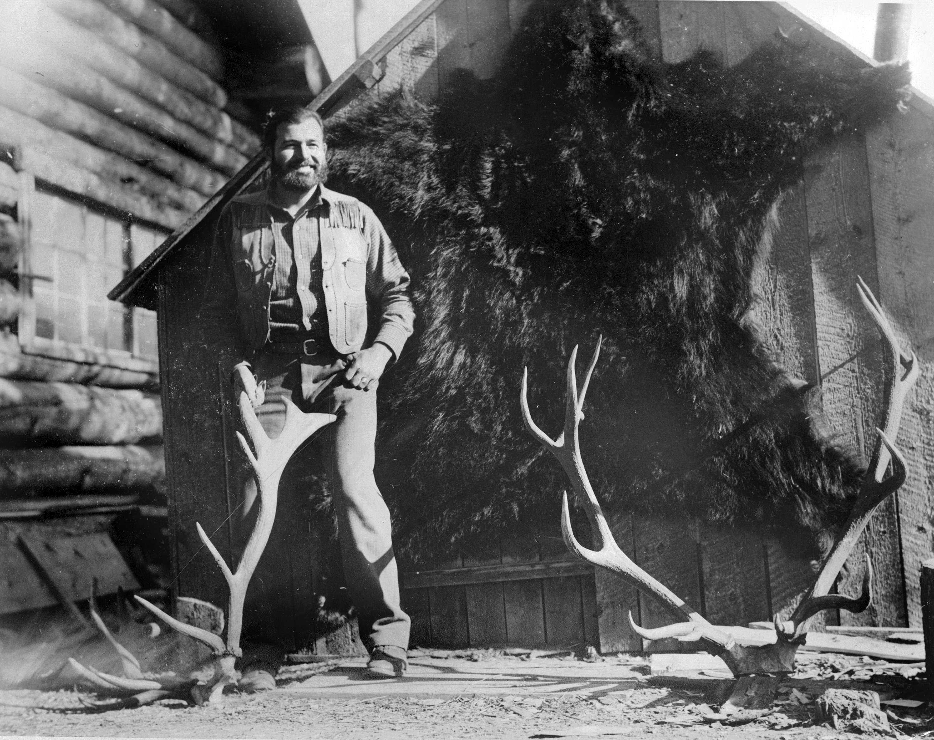 In this 1932 photo provided by the John F. Kennedy Library Foundation, Ernest Hemingway poses with a bear skin and deer antlers during a hunting trip to Nordquist's Ranch in Wyoming. (AP Photo)