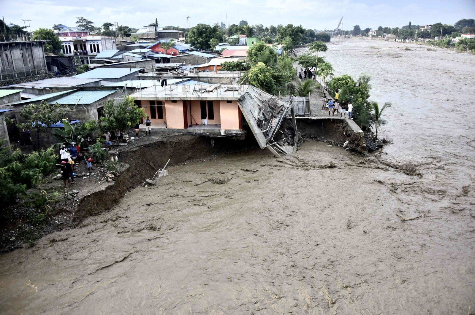 Residents stand along the water's edge by damaged homes after heavy rains and strong winds lashed East Timor's capital Dili overnight causing extensive flooding, Dili, East Timor, April 4, 2021. (AFP Photo)