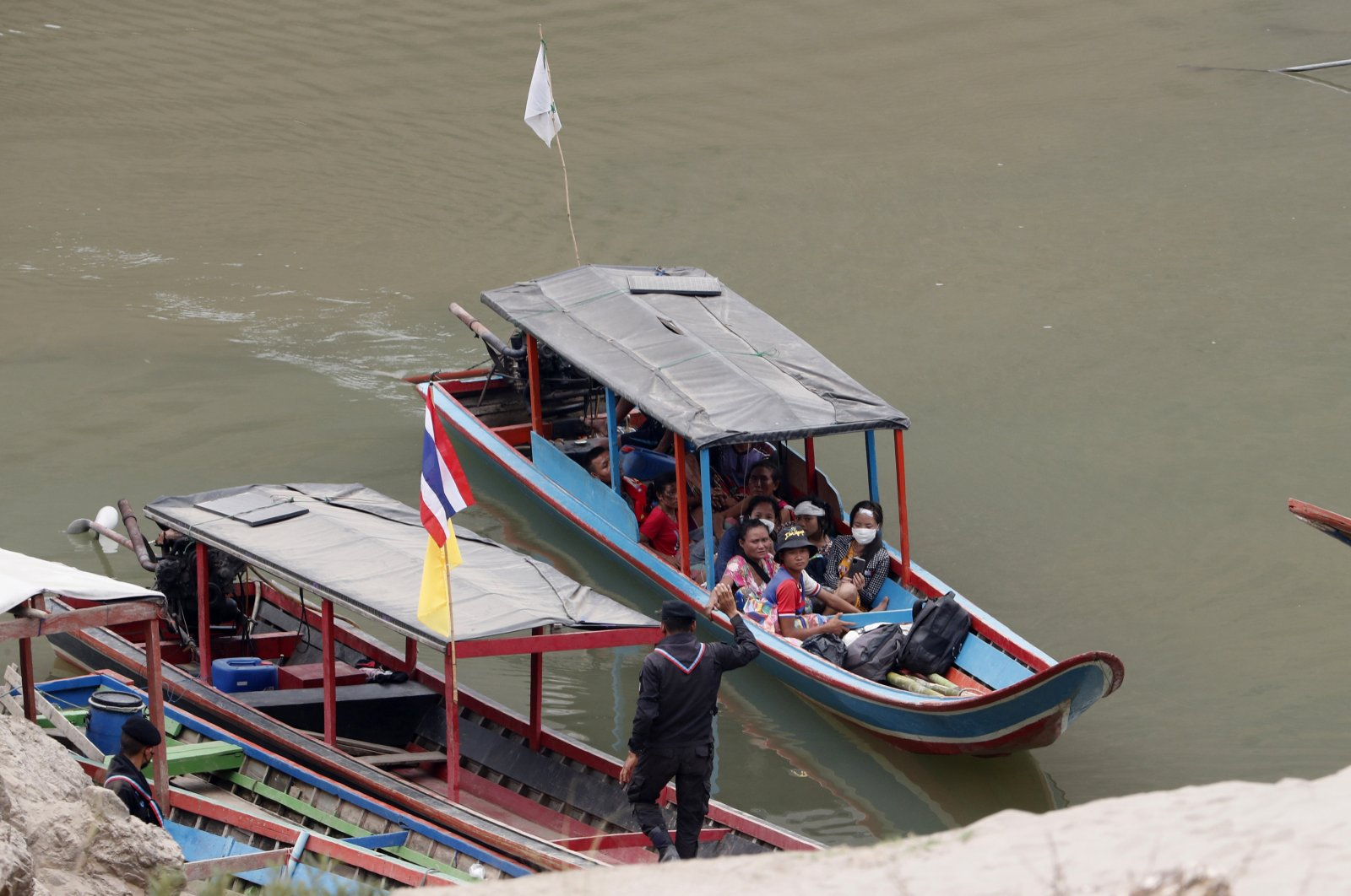 Karenni villagers from Myanmar arrive on a boat with an injured person as they evacuate to Ban Mae Sam Laep Health Center in Mae Hong Son province, northern Thailand, March 30, 2021. (AP Photo)