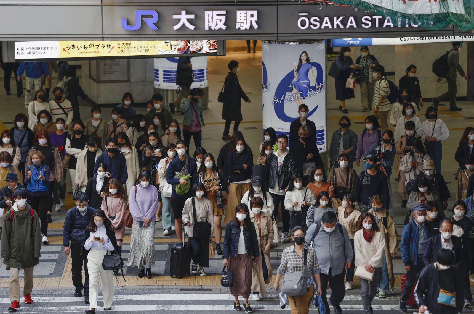 People wear face masks as they make their way in Osaka, western Japan, Wednesday, March 31, 2021. (AP Photo)