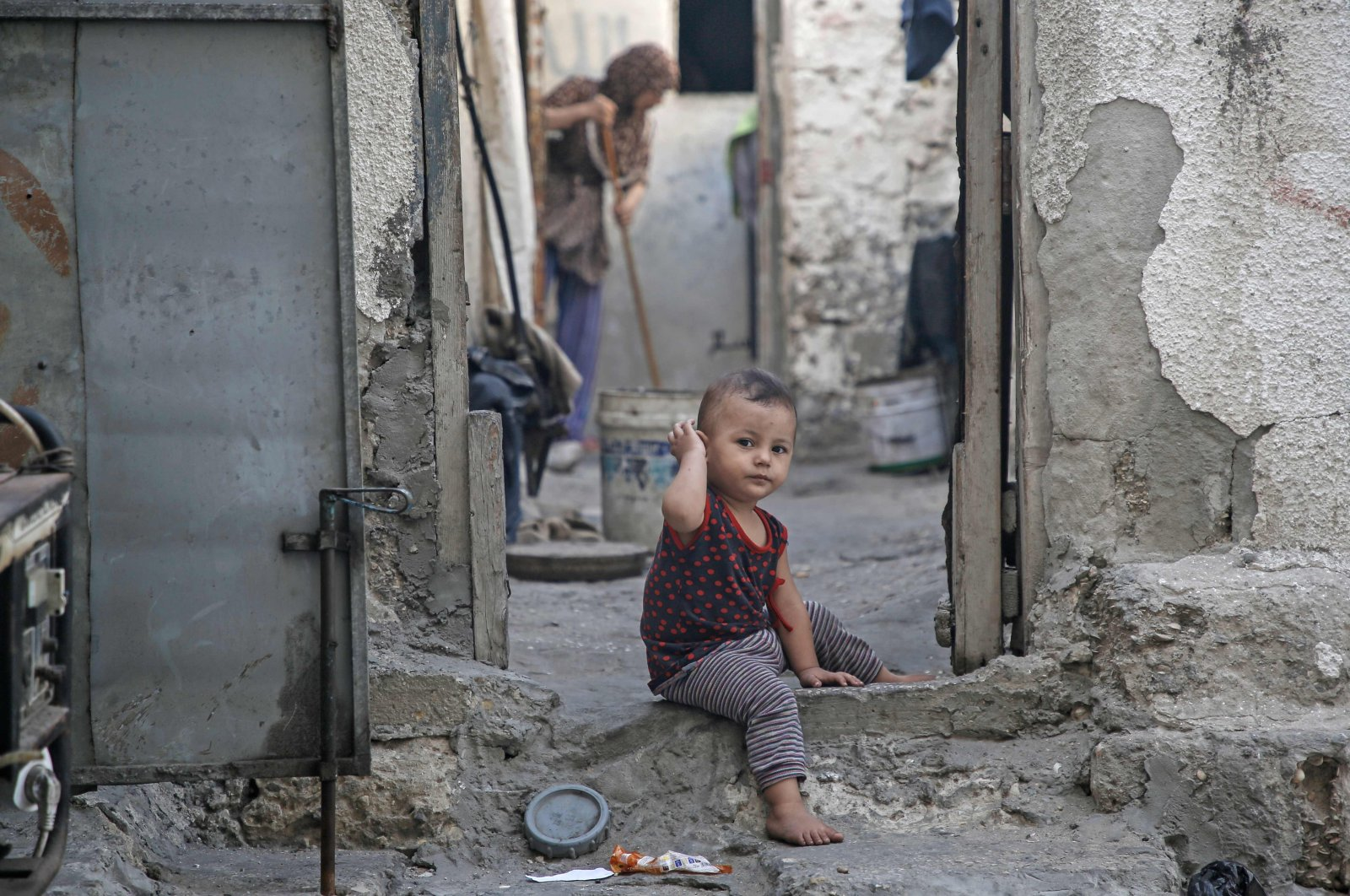 A toddler sits in a doorway of a deserted house as a woman sweeps at the Shati Palestinian refugee camp in Gaza City, Palestine, Sept. 3, 2019. (AFP Photo)