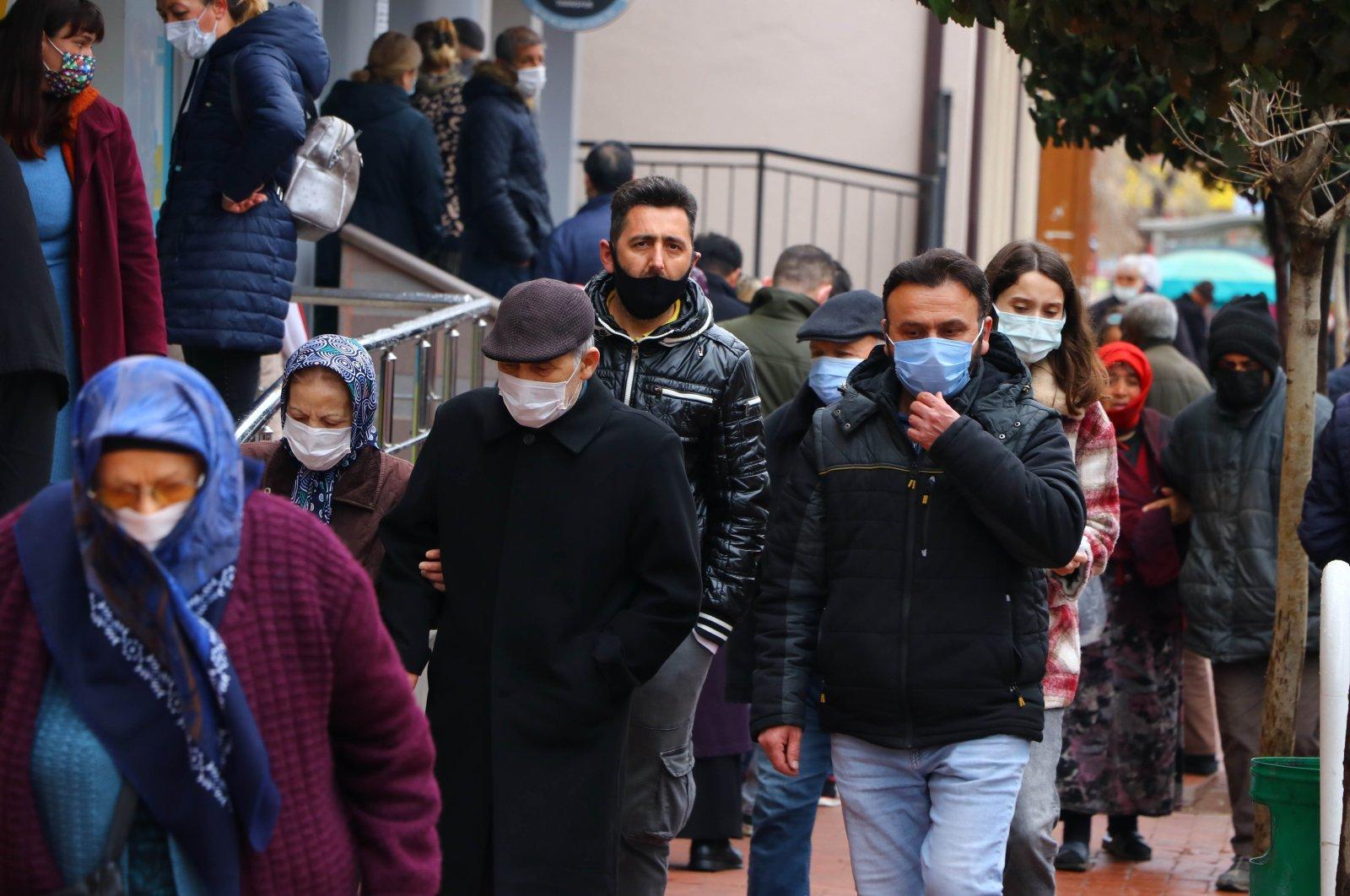 People wearing protective masks walking on a street in Tekirdağ, northwestern Turkey, April 5, 2021. (AA PHOTO)