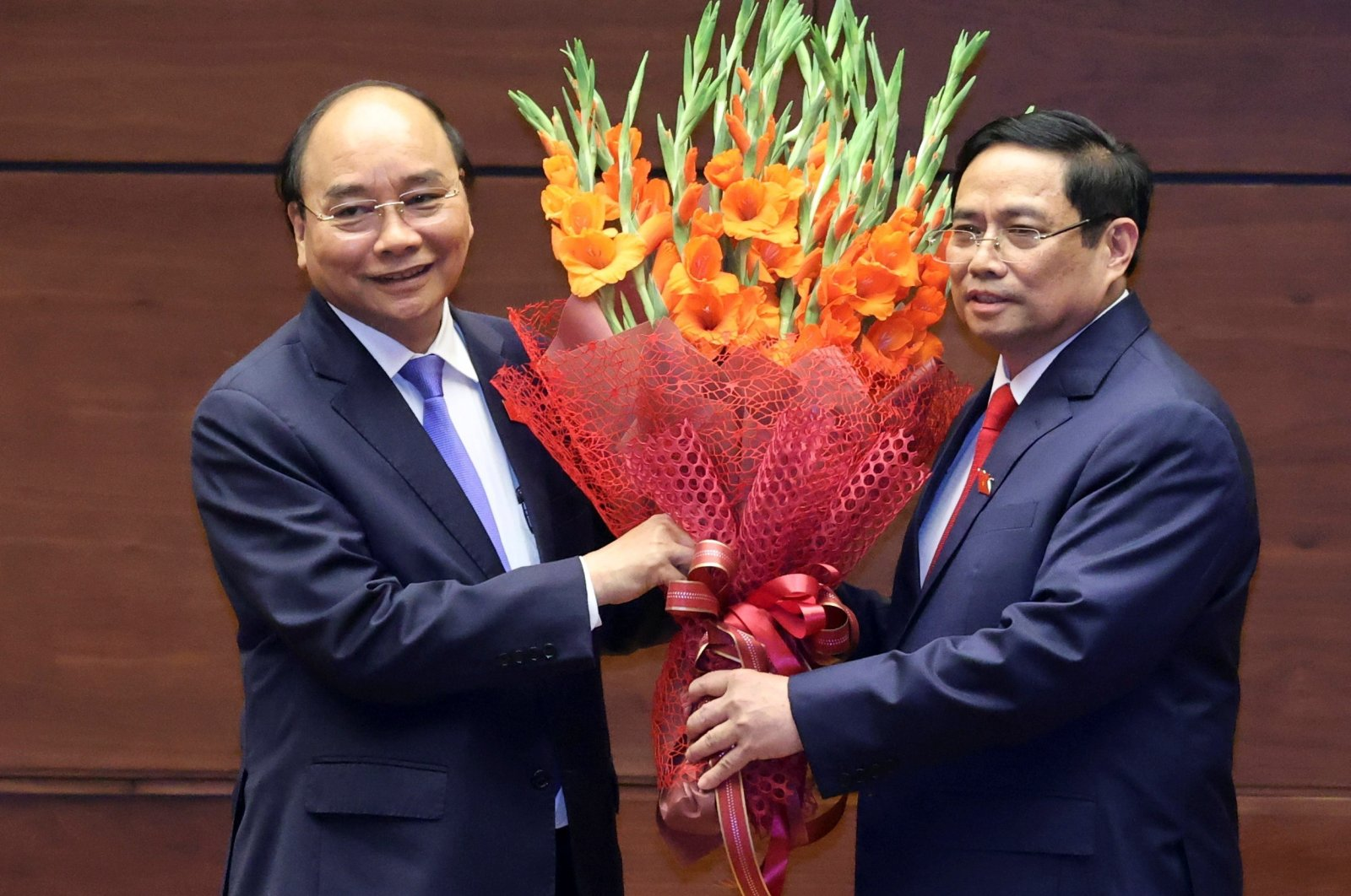 Vietnam's new prime minister, Pham Minh Chinh (R), holds a bouquet of flowers with the country's former prime minister,  Phuc, who became the new president, at an official ceremony in Hanoi, Vietnam, April 5, 2021. (VNA via Reuters)
