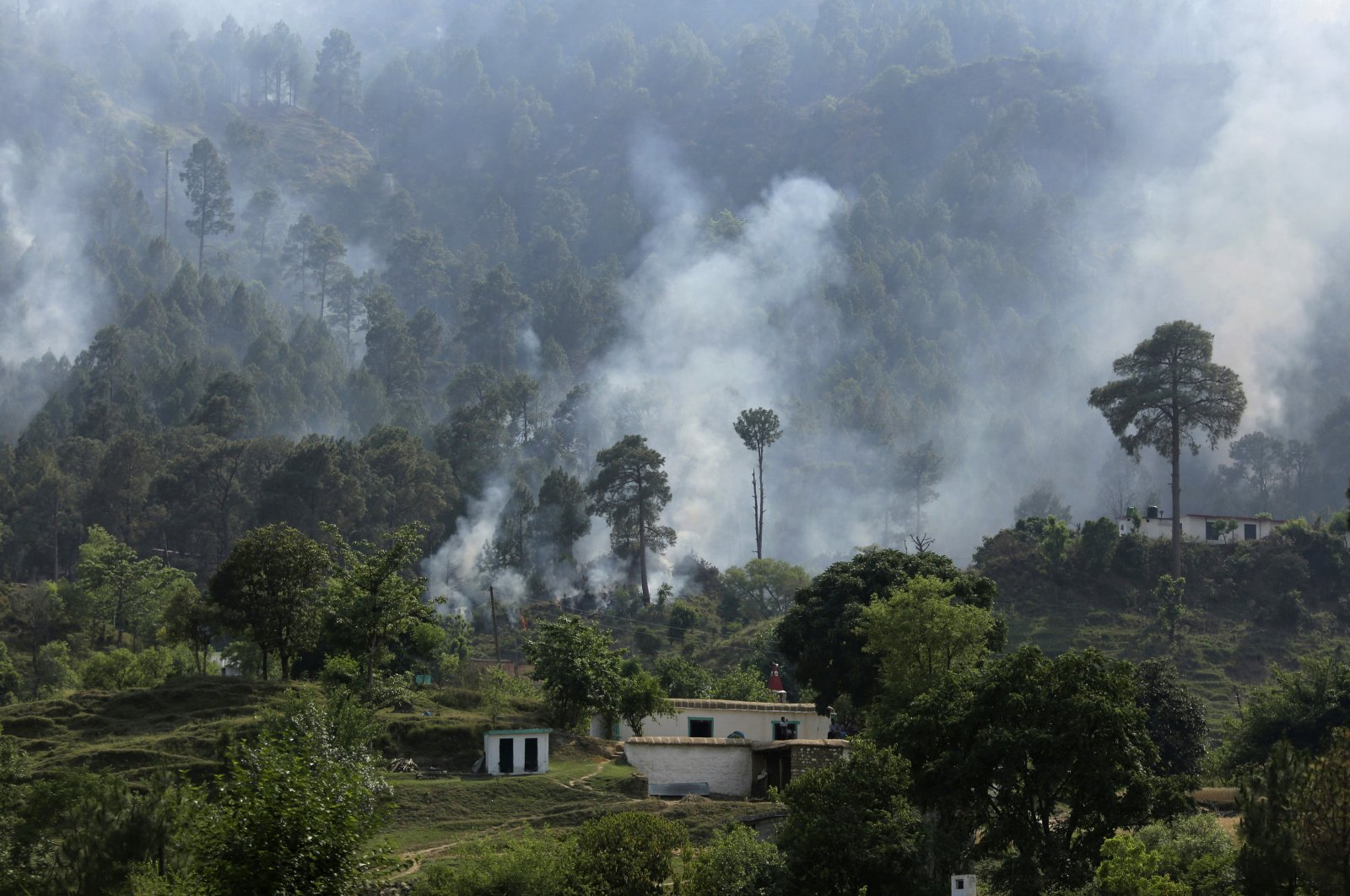 Smoke rises from a mortar shell fired from the Pakistan side of the border in a civilian area at Bhawani village at Nowshera sector, along the highly militarized Line of Control that divides the region between India and Pakistan, May 13, 2017. (AP Photo)