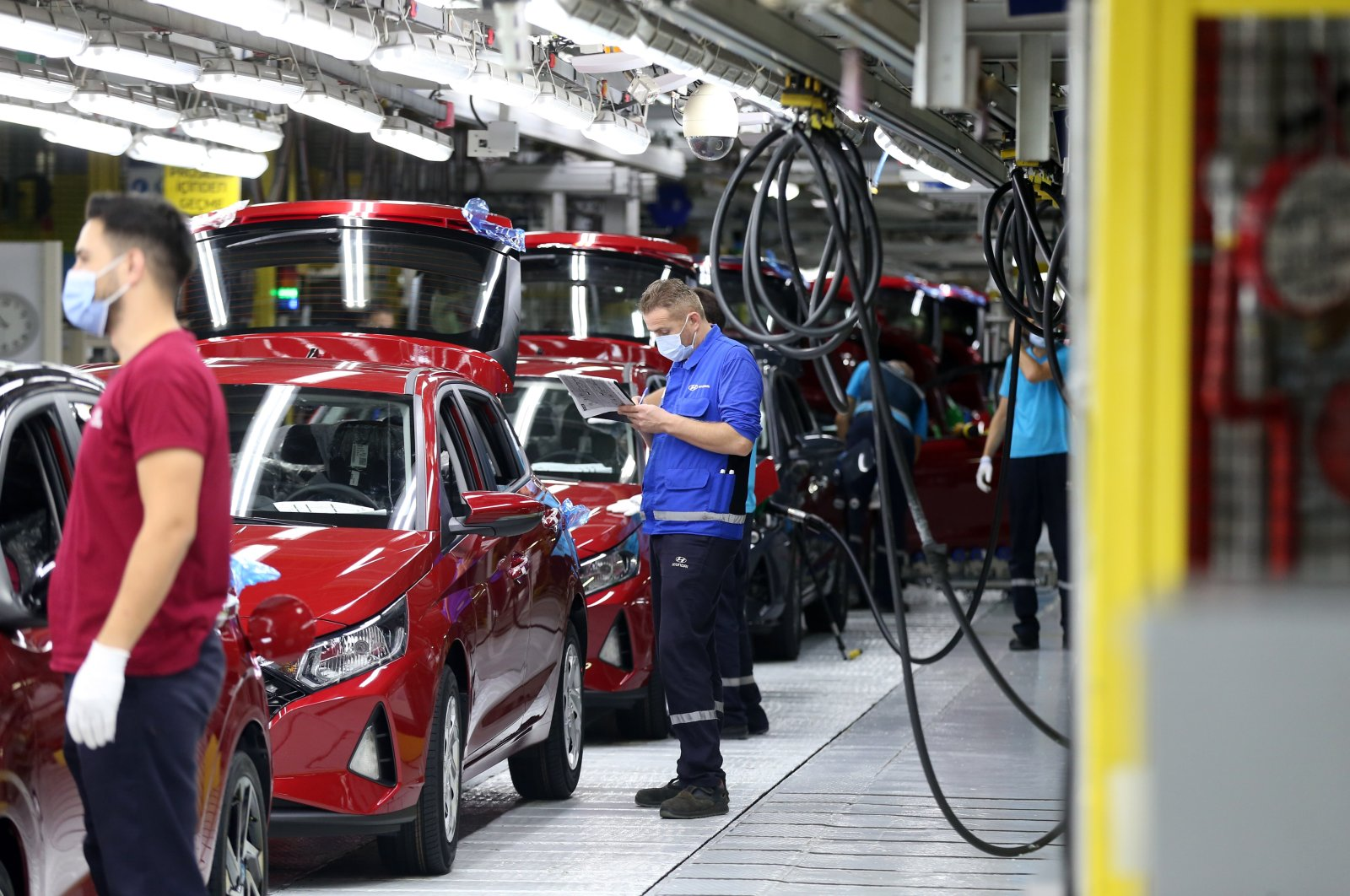 Workers are seen beside new i20 model cars at Hyundai Assan's Izmit factory in northwestern Kocaeli, Turkey, Aug. 28, 2020. (AA Photo)