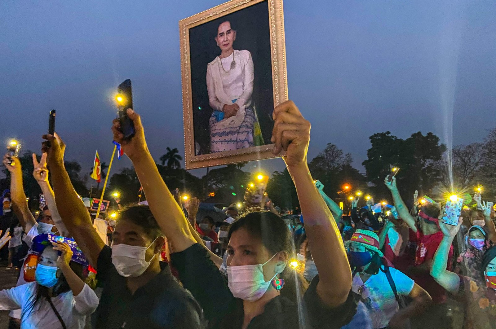 A Myanmar migrant living in Thailand holds a portrait of detained civilian leader Aung San Suu Kyi while others hold up their mobile phone lights during a night protest against the military coup in their homeland, Chiang Mai, Thailand, April 4, 2021. (AFP Photo)