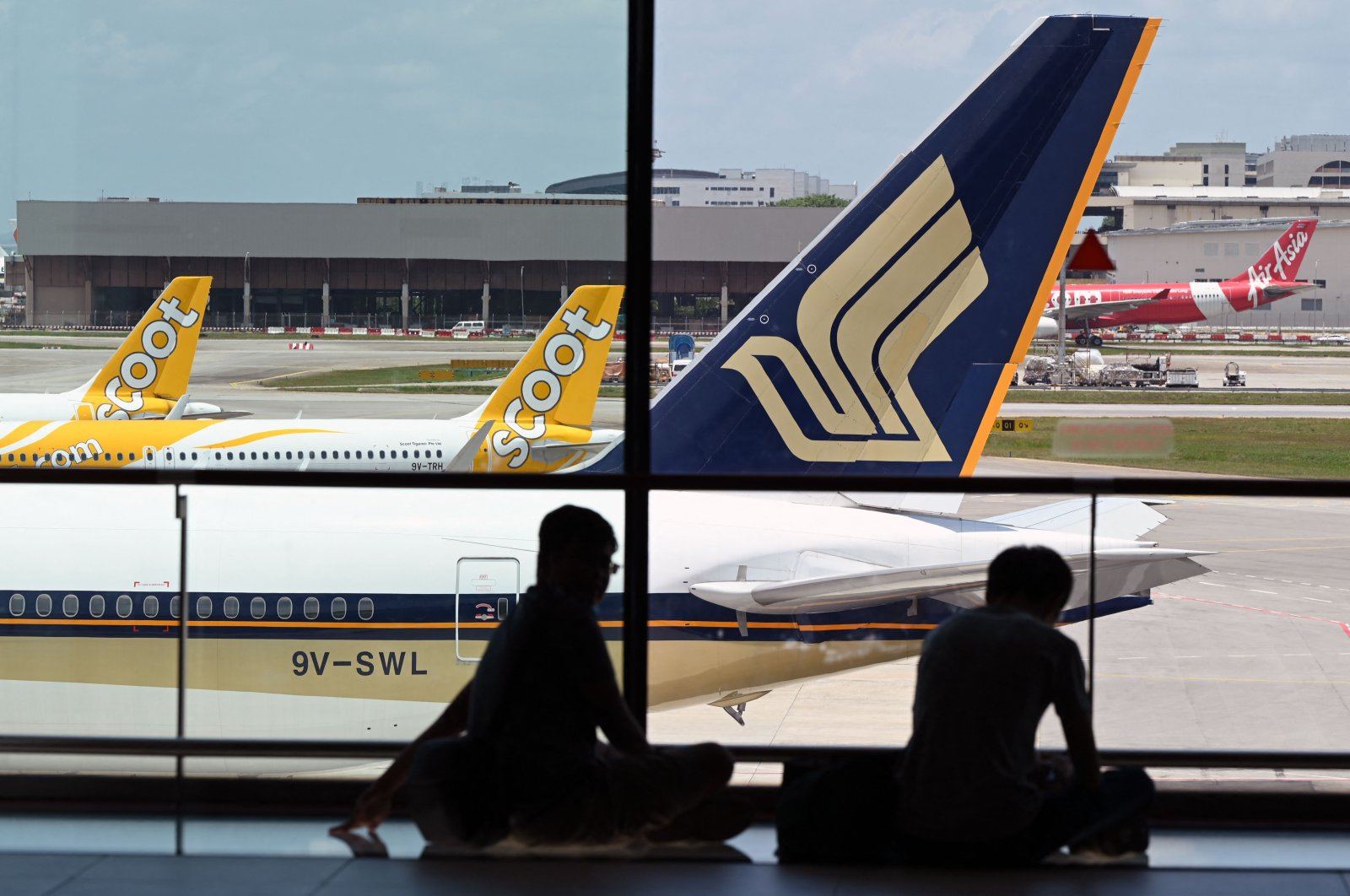 A Singapore Airlines plane is parked beside Scoots passenger planes on the terminal tarmac at Changi International Airport in Singapore, March 15, 2021. (AFP Photo)