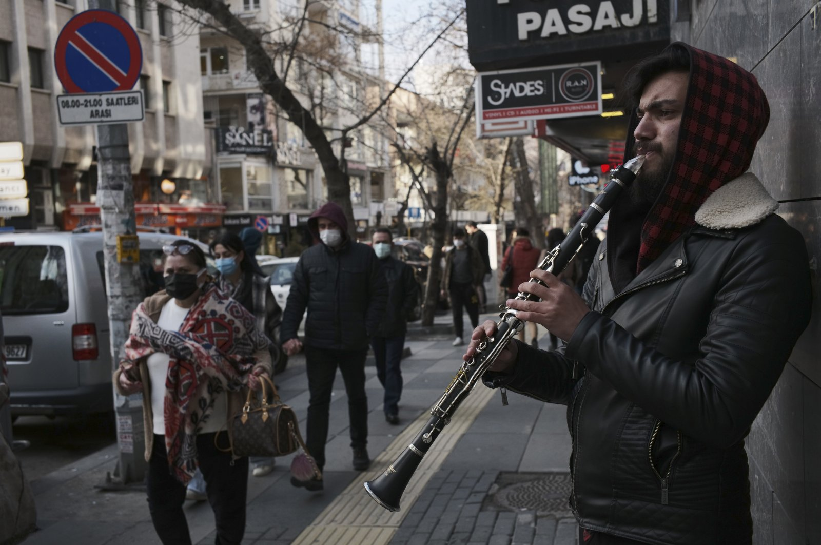 People wearing masks to help protect against the spread of coronavirus, walk past a musician in Ankara, Turkey, April 2, 2021. (AP Photo/Burhan Ozbilici)