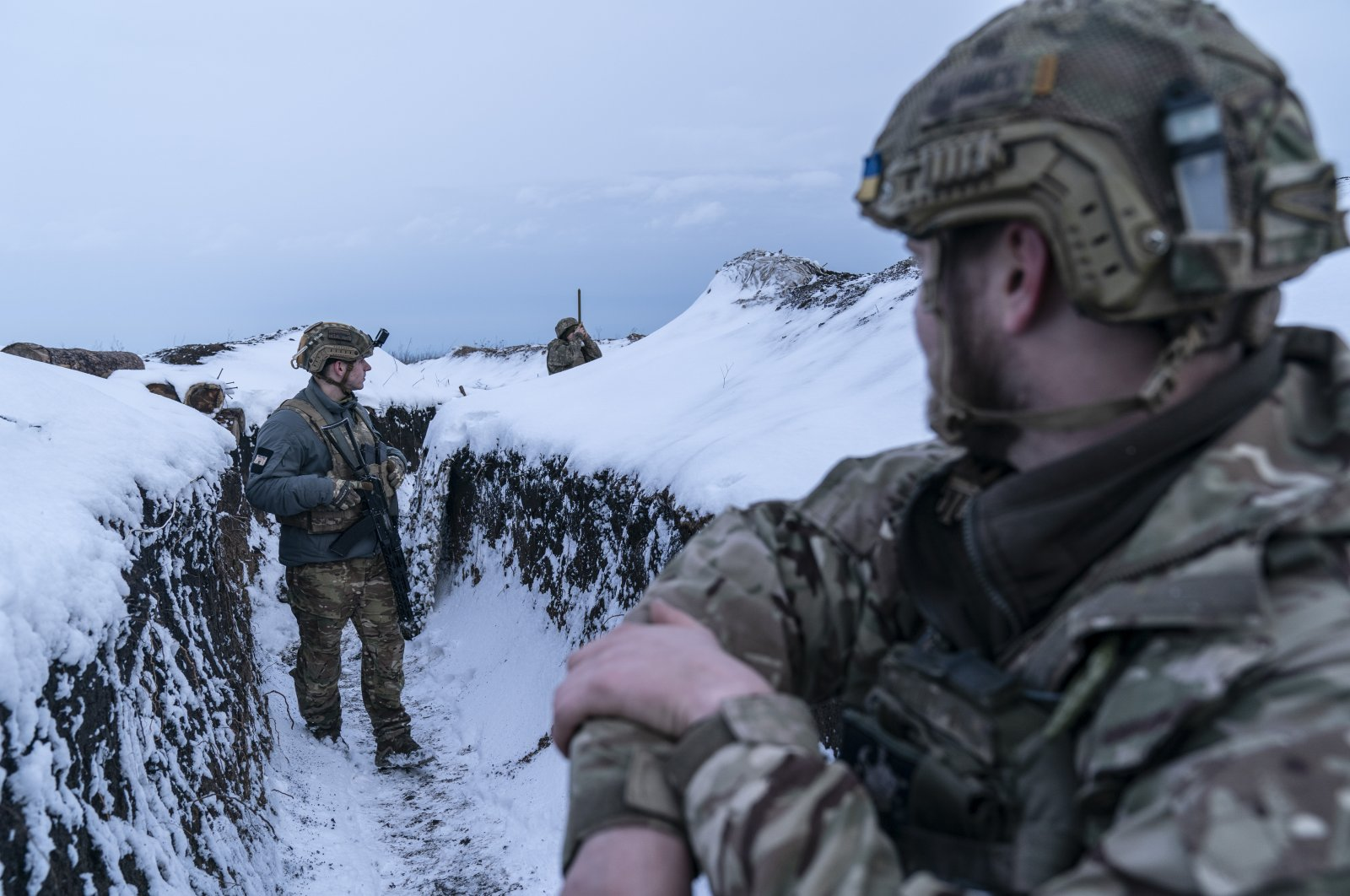 Ukrainian servicemen walk along a snow-covered trench guarding their position at the frontline near Vodiane, about 750 kilometers (468 miles) southeast of Kyiv, eastern Ukraine, March 5, 2021. (AP Photo)