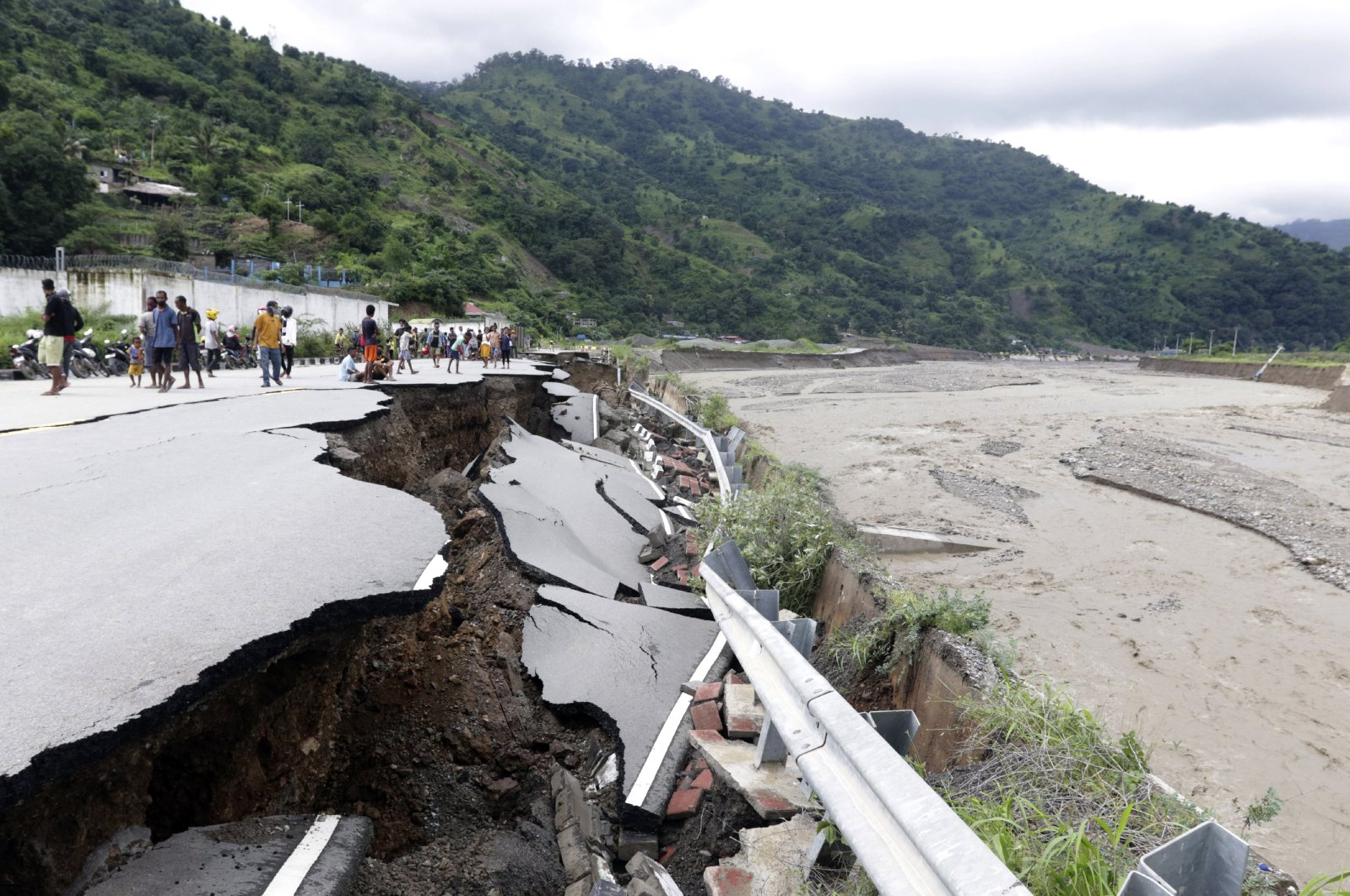 Residents inspect a damaged road following a flood in Dili, East Timor, April 5, 2021. (AP Photo)